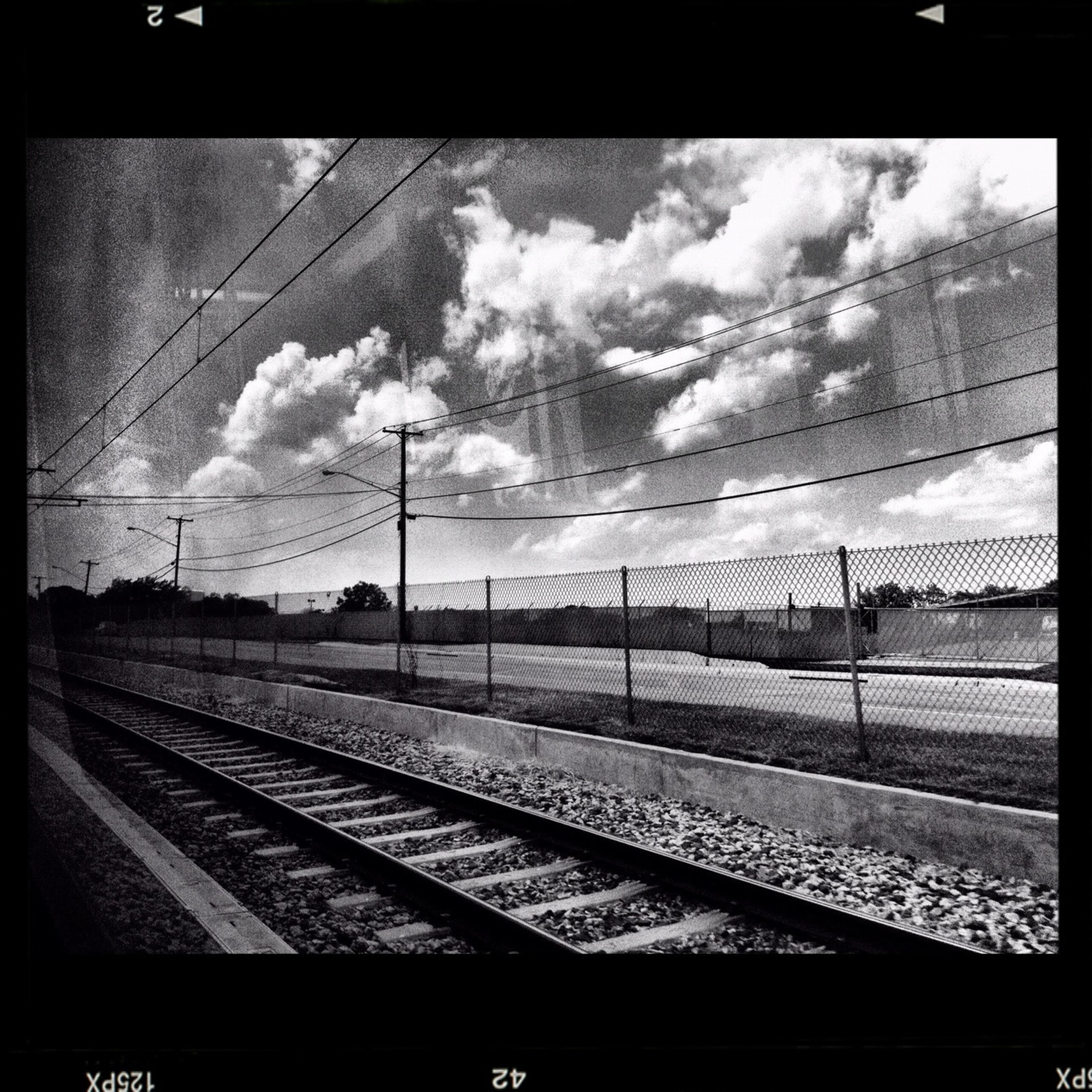 transfer print, power line, railroad track, transportation, sky, electricity pylon, rail transportation, power supply, cloud - sky, auto post production filter, cable, connection, electricity, public transportation, railroad station platform, railroad station, cloudy, power cable, cloud, train - vehicle