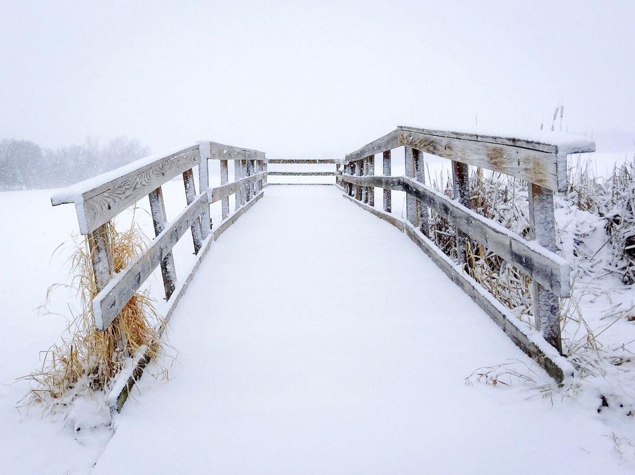Snow Covered Footbridge Against Sky