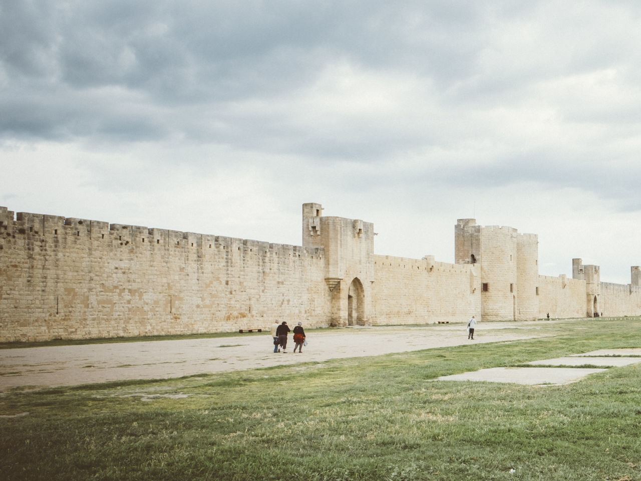 People At Remparts Daigues-Mortes Against Cloudy Sky