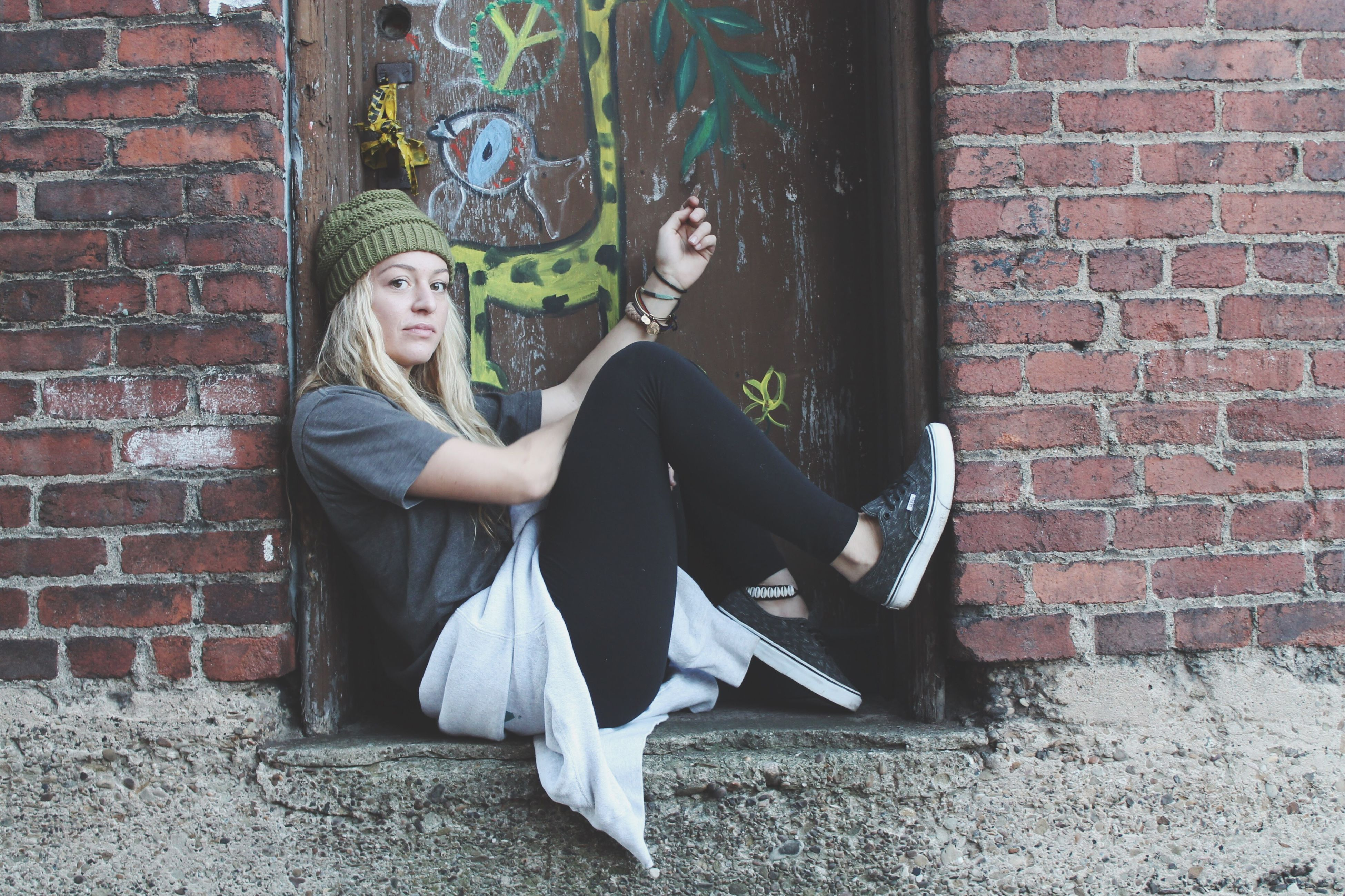young adult, young women, brick wall, lifestyles, casual clothing, wall - building feature, front view, person, standing, building exterior, leisure activity, built structure, architecture, full length, long hair, looking at camera, portrait