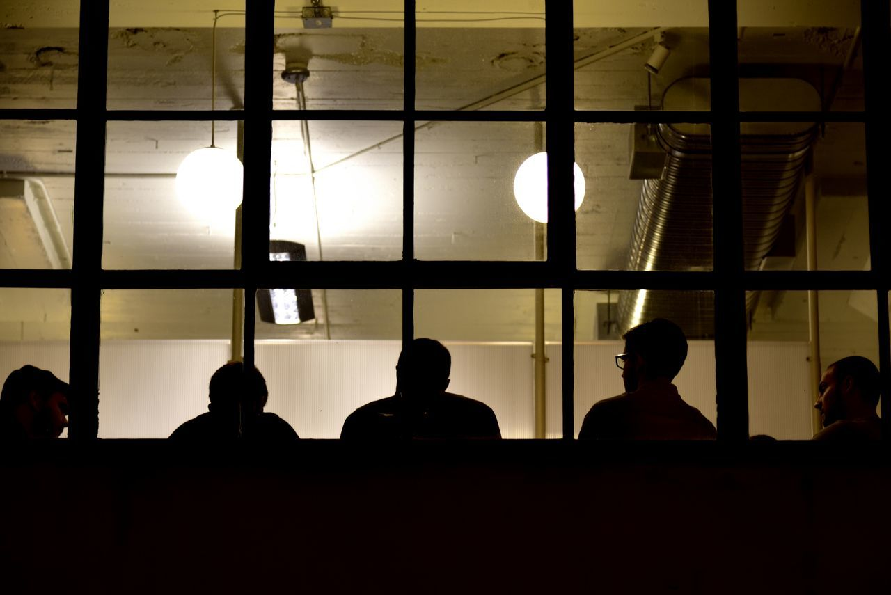 Employees at night in a meeting silhouetted through a window. Adult Airport Back Lit Business Employees Engineers Horizontal Illuminated Indoors  Late Meeting Men Midnight Oil Night Nightphotography Occupation Office Office People Person Real People Silhouette Standing Watching Window