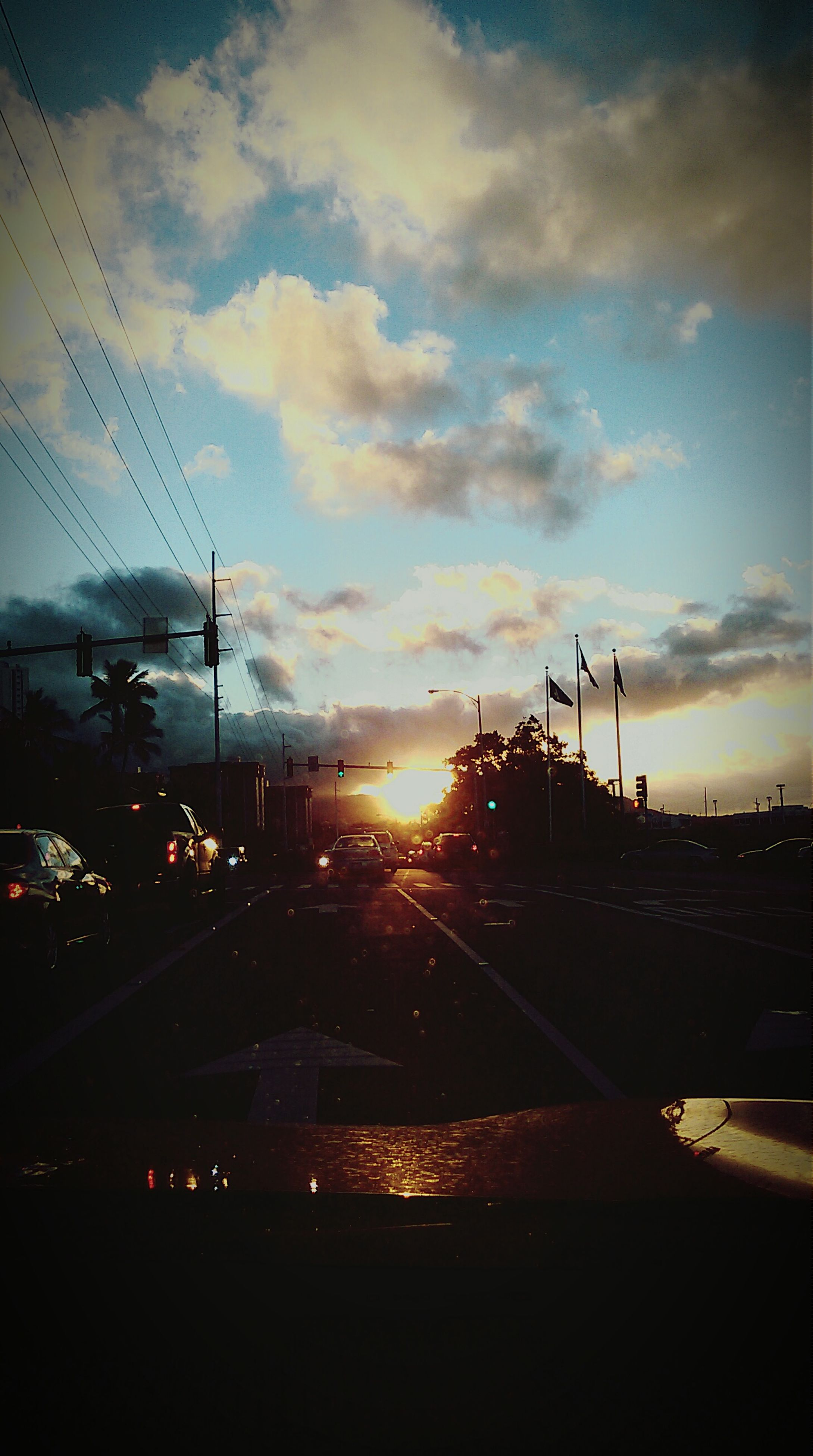 sunset, transportation, mode of transport, sky, car, sun, cloud - sky, land vehicle, orange color, road, silhouette, street light, street, sunlight, cloud, travel, no people, lens flare, on the move, cloudy