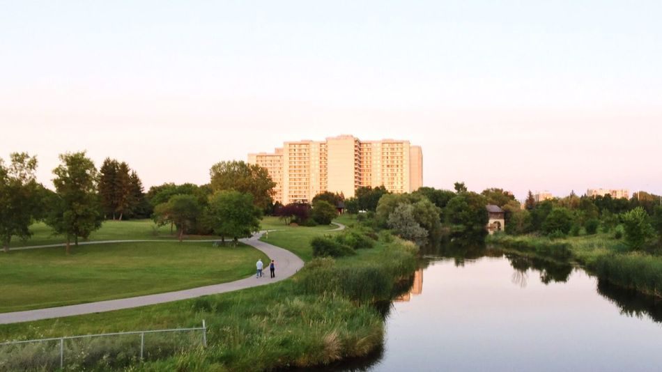 An elderly couple strolling along Sturgeon Creek in Winnipeg, Canada. Tree Architecture City Clear Sky Building Exterior Built Structure Nature Grass No People Growth Day Beauty In Nature Sky Outdoors Scenics Landscape (null)Creekside Trail Creekscapes Urban Reflections Water Reflection Creek Urban Path Park Path Mills