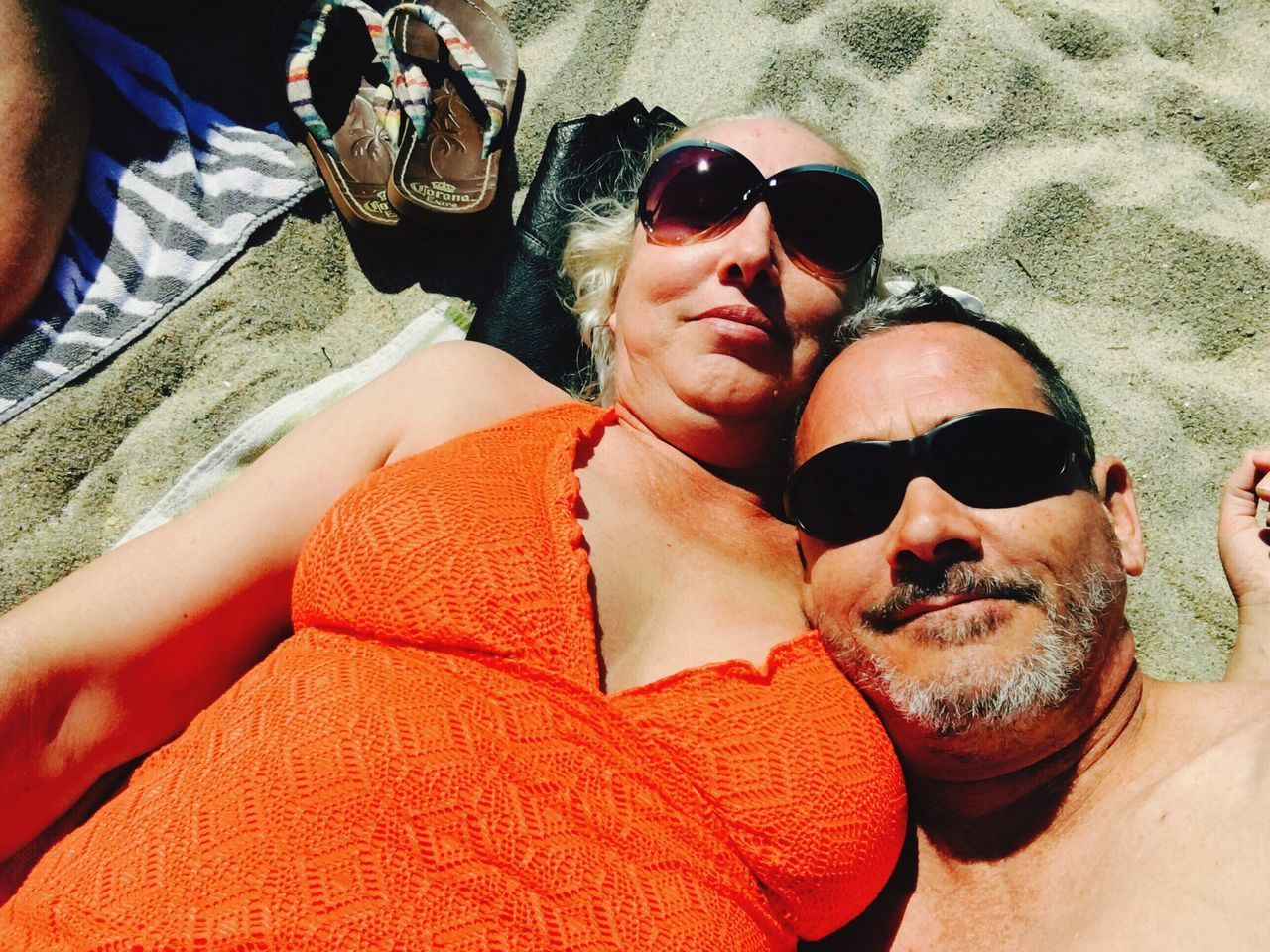 High Angle View Of Mature Couple Resting At Beach On Sunny Day