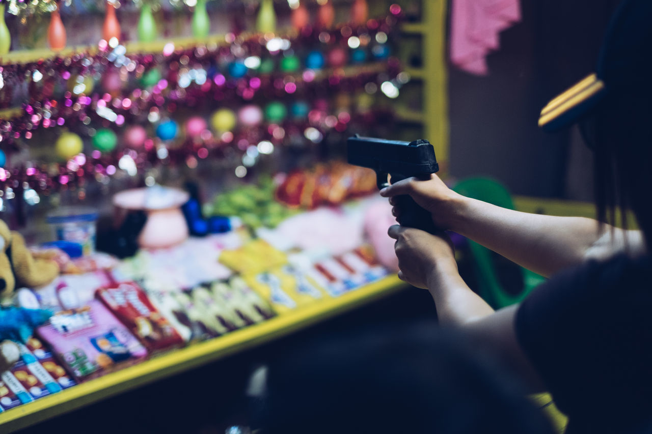 Street and night photography: Girl on target shooting booth Aim Booth Carnaval Crowd Festival Game Game Of Chance Gun Hands Holding Human Body Part Human Hand Luck Night Photography People Precision Reward Street Photography Target Target Shooting Toy Gun EyeEmNewHere