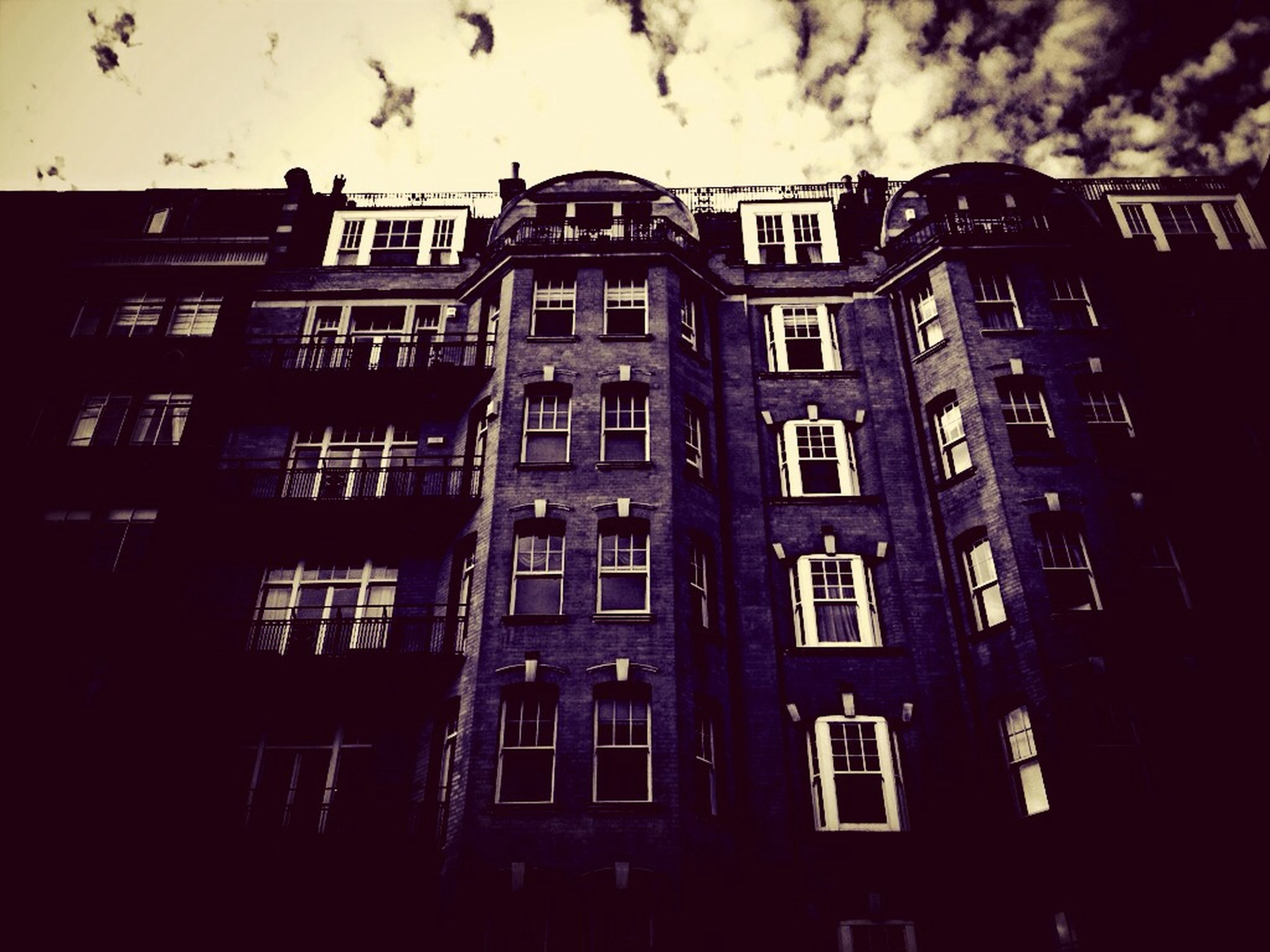building exterior, architecture, built structure, window, low angle view, building, residential building, sky, residential structure, city, apartment, outdoors, day, no people, house, facade, exterior, balcony, cloud - sky, city life