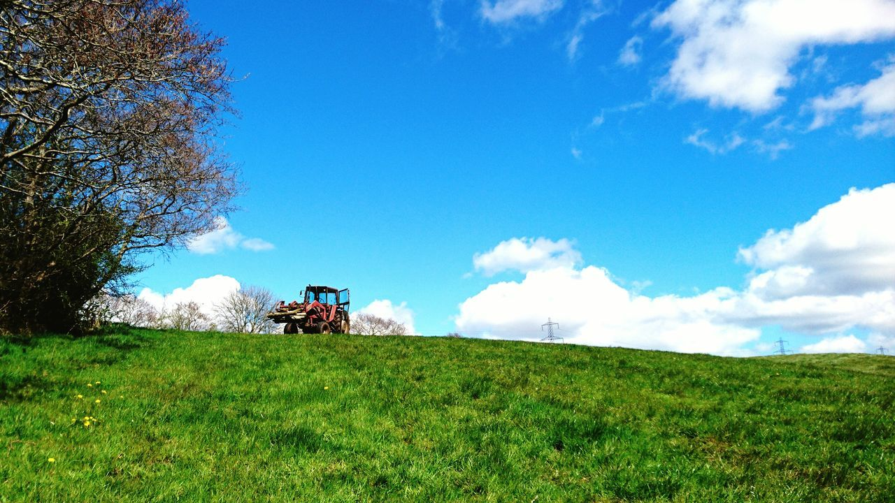 field, agriculture, farm, grass, agricultural machinery, sky, transportation, tractor, nature, rural scene, day, landscape, green color, cloud - sky, land vehicle, tree, growth, mode of transport, outdoors, beauty in nature, scenics, combine harvester, no people