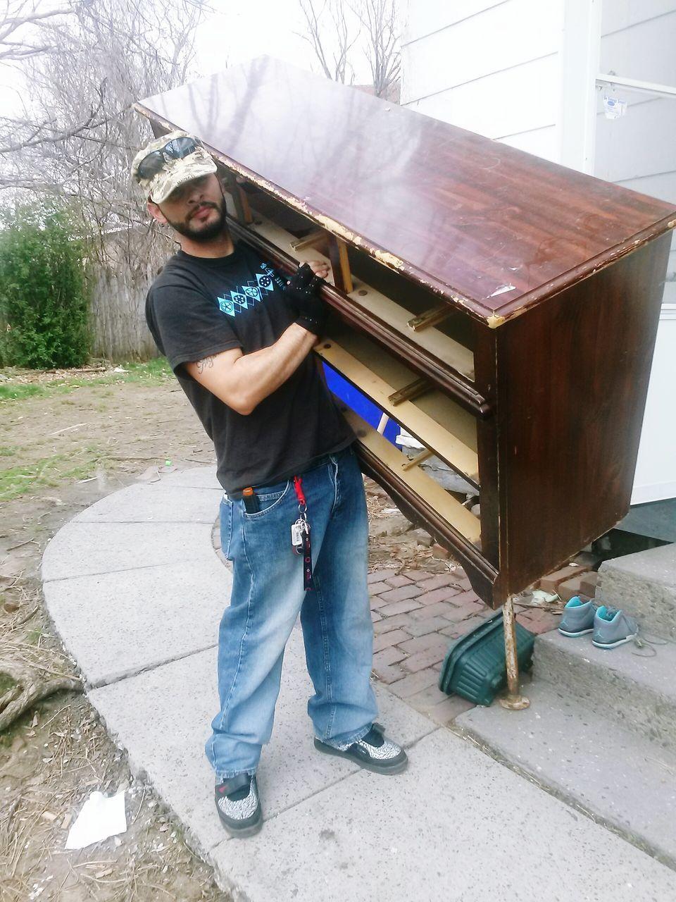 Man Holding Broken Furniture Outdoors