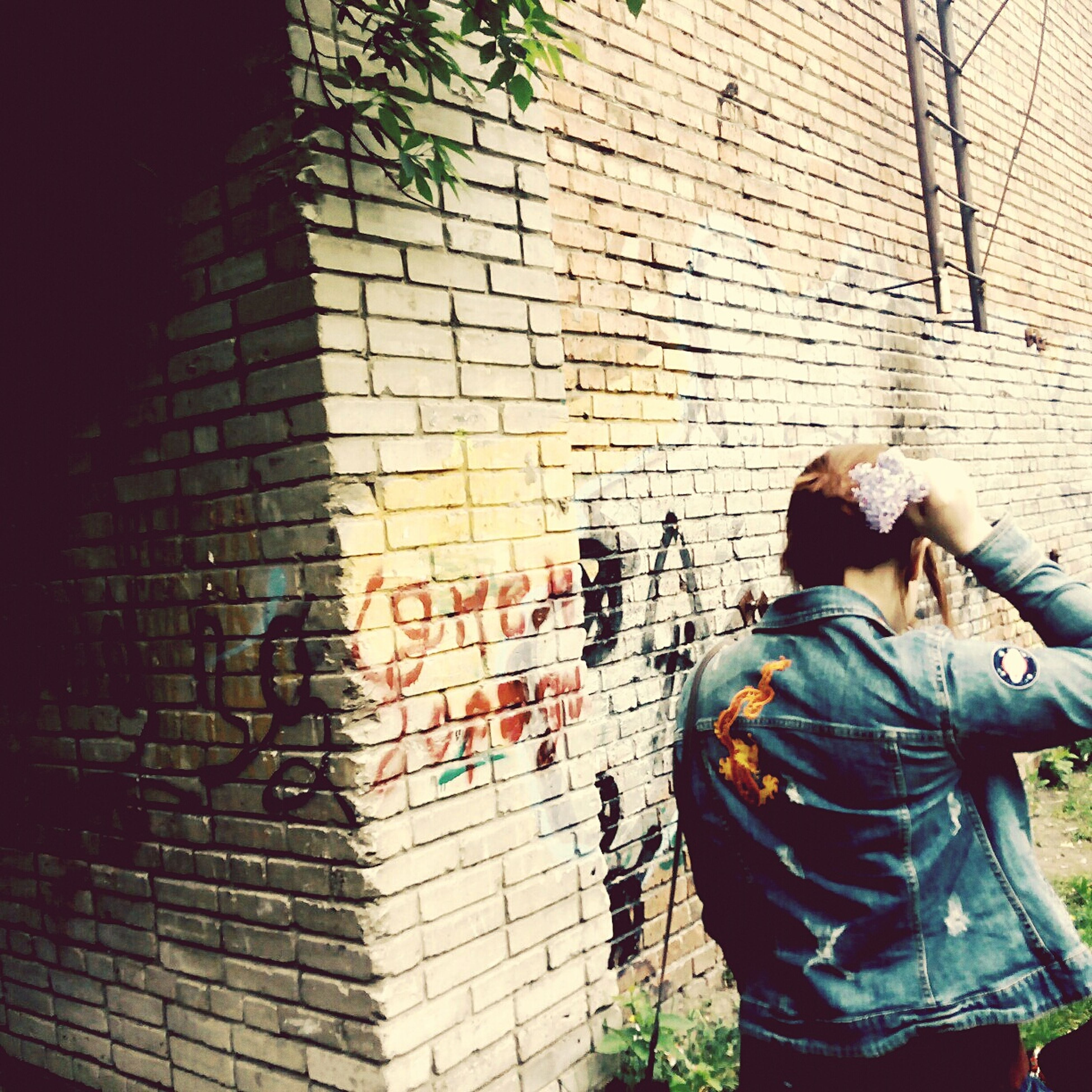 lifestyles, casual clothing, leisure activity, built structure, men, architecture, building exterior, standing, rear view, graffiti, wall - building feature, full length, three quarter length, young adult, communication, outdoors, day