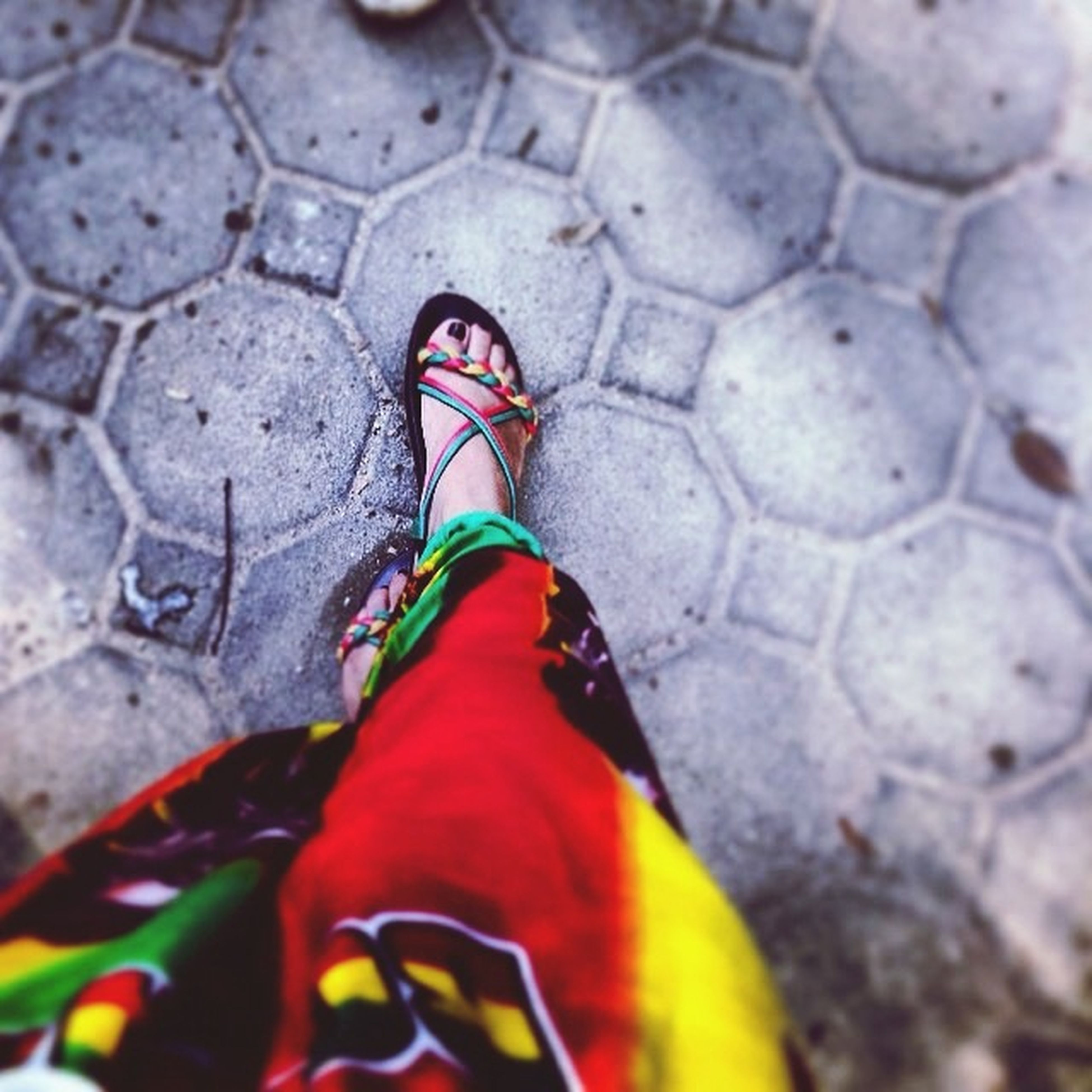 low section, shoe, person, high angle view, footwear, close-up, pattern, multi colored, ground, textured, red, day, outdoors, unrecognizable person, human foot, part of, pair