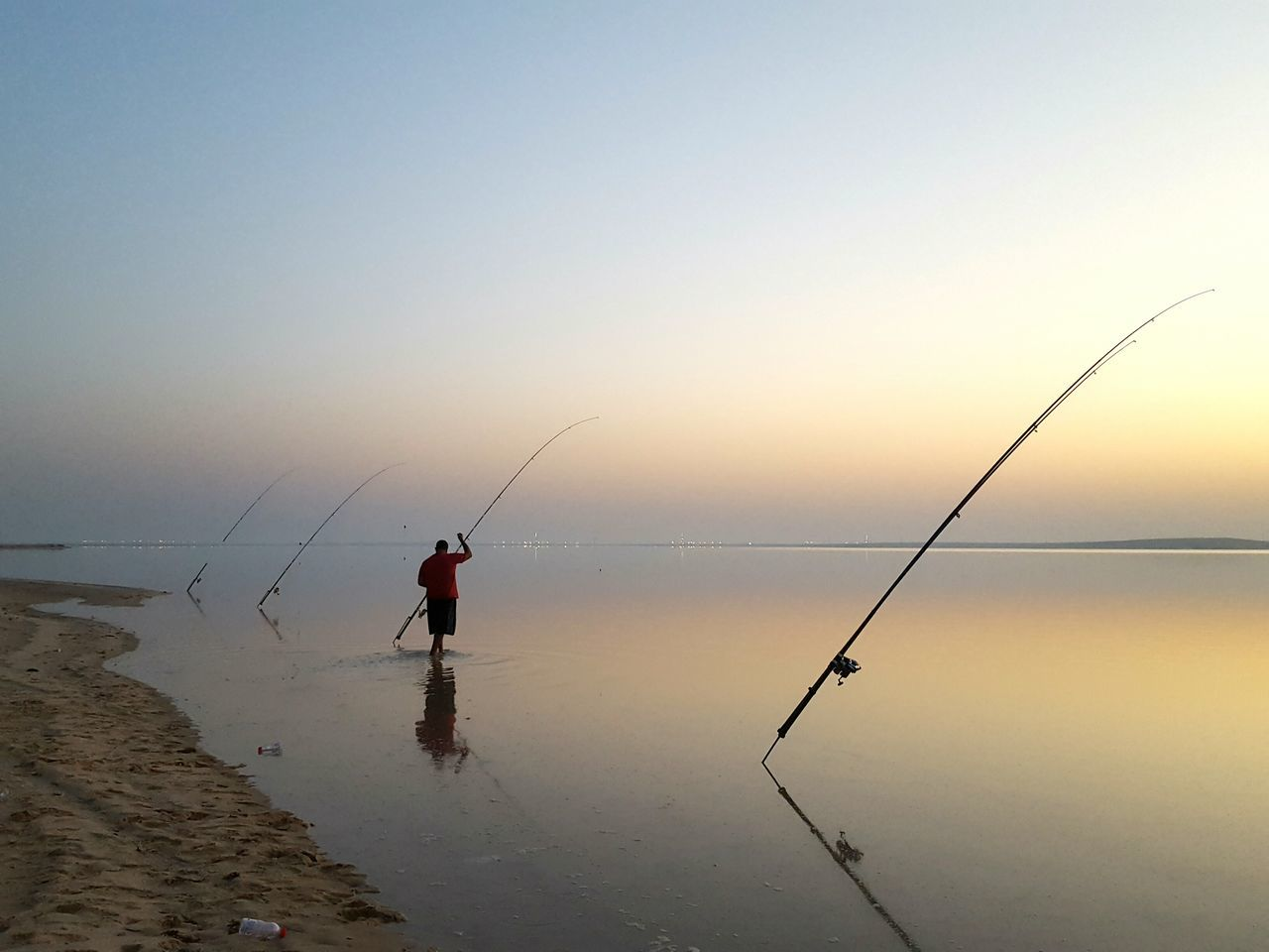 Rear View Of Man Fishing In Sea Against Clear Sky During Sunset