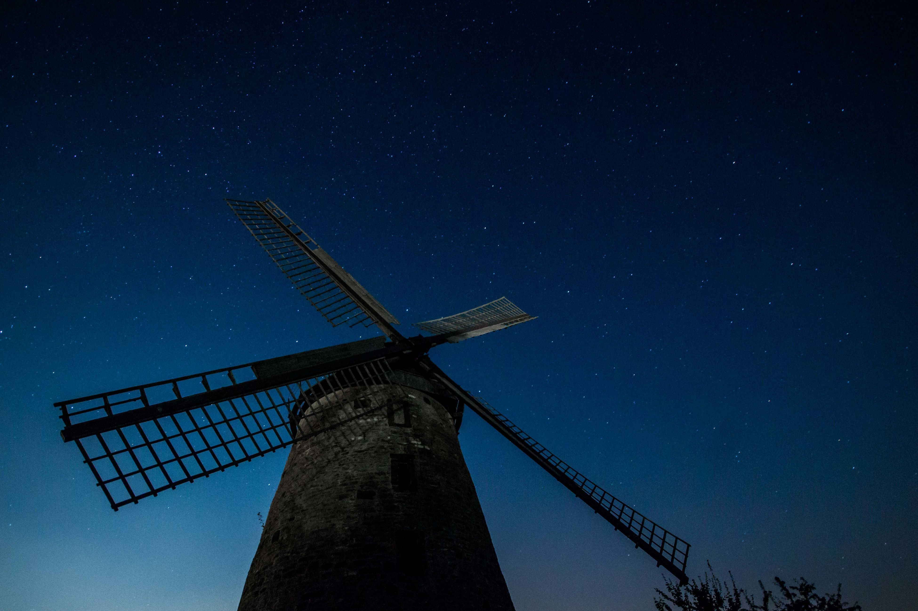 low angle view, alternative energy, wind power, wind turbine, fuel and power generation, windmill, renewable energy, environmental conservation, sky, technology, traditional windmill, built structure, silhouette, night, industry, crane - construction machinery, outdoors, smoke stack, no people, clear sky