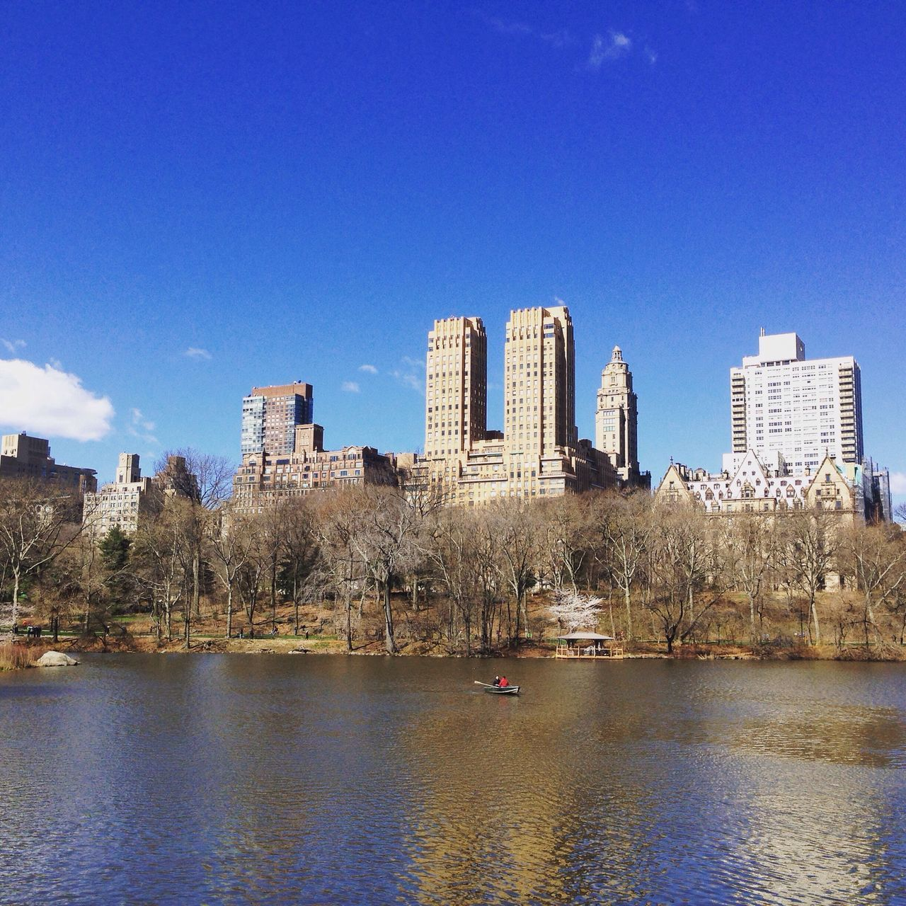 architecture, building exterior, built structure, city, skyscraper, blue, cityscape, water, waterfront, tower, urban skyline, day, skyline, city life, outdoors, modern, river, travel destinations, no people, sky, clear sky, tall, growth, nature