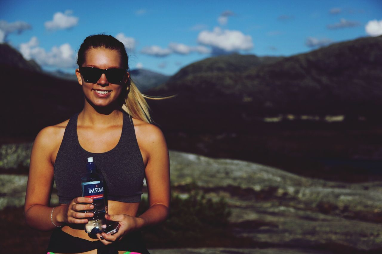 sunglasses, young adult, outdoors, mountain, one person, front view, smiling, real people, young women, lifestyles, sky, nature, happiness, focus on foreground, water, looking at camera, leisure activity, day, beauty in nature, portrait, beautiful woman