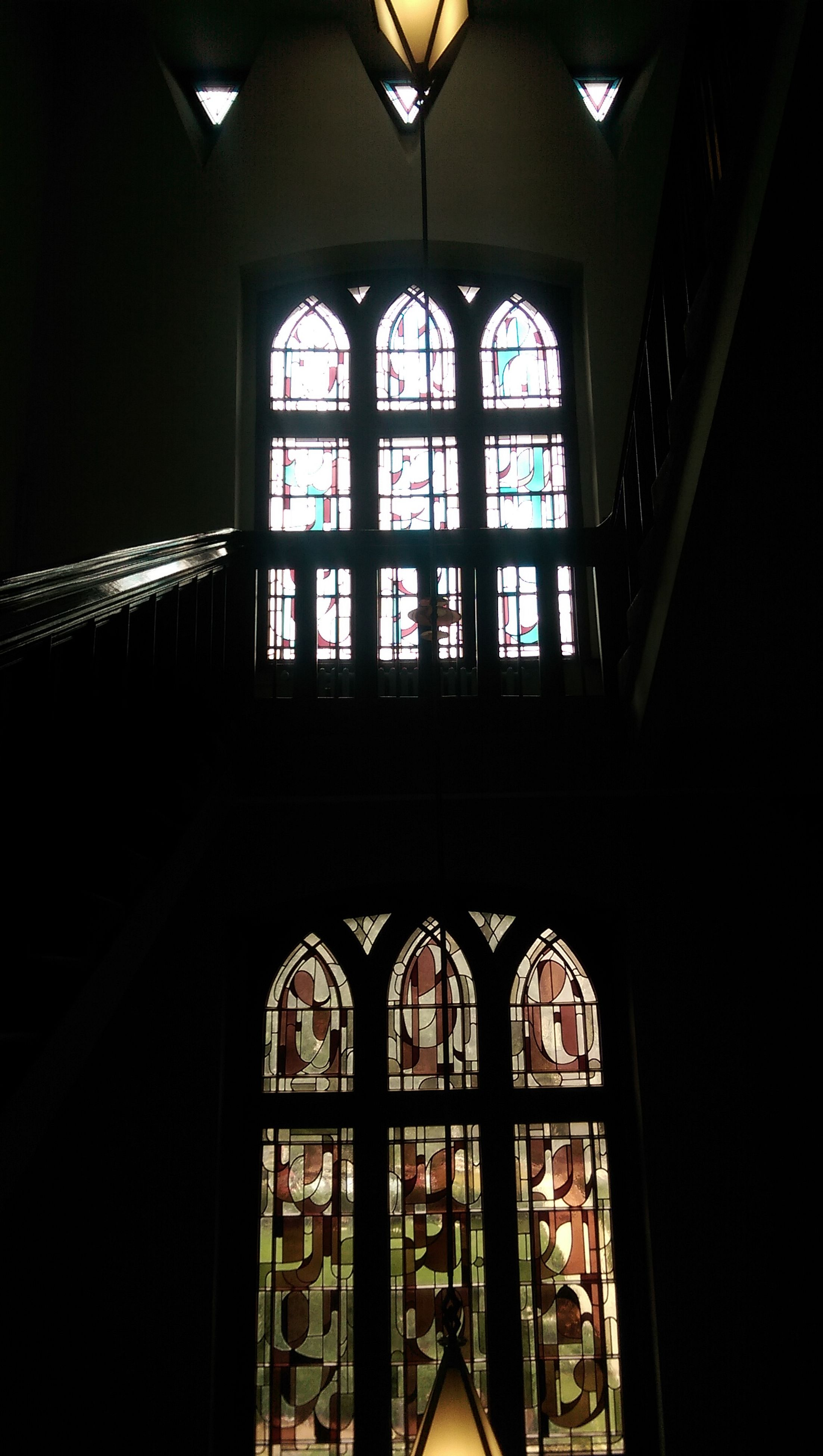 indoors, window, architecture, built structure, arch, glass - material, church, interior, place of worship, stained glass, ceiling, religion, illuminated, home interior, transparent, spirituality, dark, low angle view, no people