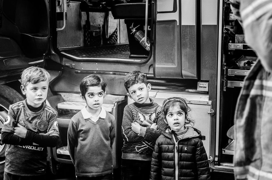 Four pairs of curious eyes look on with awe as the fireman puts on his outfit and shows them the fire engine's parts. 4 Kids Attention Awe Awestruck Bewildered Boys Childhood Children Curious Day Demonstration Education Fire Engine Fire Station Fire Truck Girls Indoors  Kids Being Attentive Novel Real People Safety Standing Starting Young Teaching Training