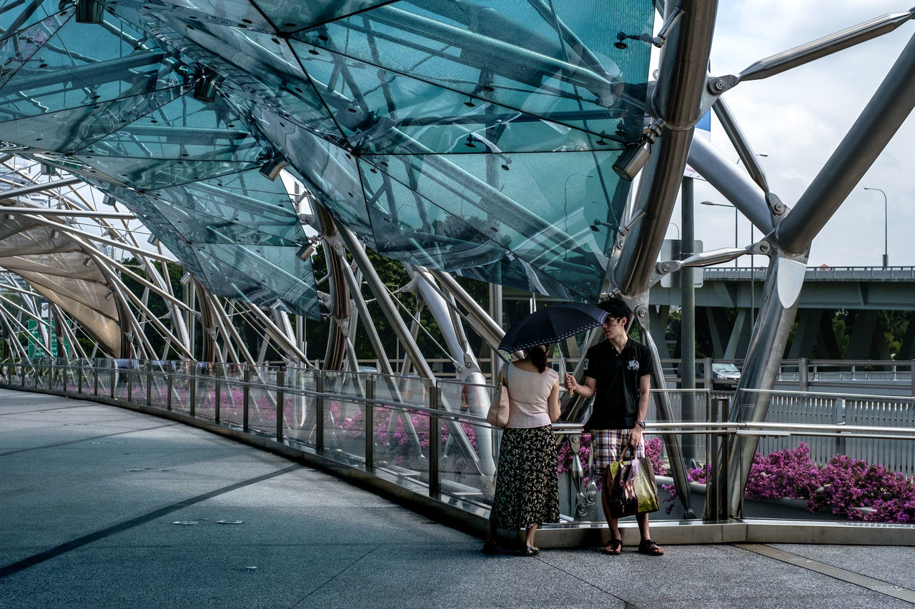 This is the direct opposite of what I have captured in my previous image. I personally feel that it is more manly for a man to hold a umbrella for his loved one, than for a man to carry her handbag for her. http://www.instagram.com/anyhow.shoot Architecture Built Structure Bridge - Man Made Structure City Railing Travel Destinations Outdoors People Adults Only Helix Bridge Singapore Umbrella Couple Romance Lovers Street Photography Streetphotography Streetphoto_color Streetlife Street Life Everybodystreet Fujifilm X-Pro1