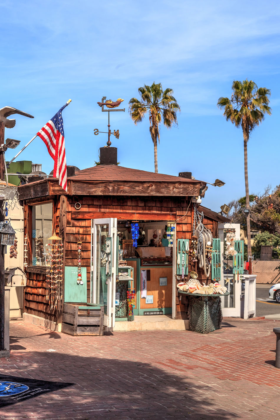 Laguna Beach, California, April 22, 2017: Building near Main Beach in downtown Laguna Beach where sea shells and jewelry are sold. Editorial use only. Architecture Beach Town Building Exterior Built Structure California Coastal Coastline Day Flag Laguna Beach, CA Nature No People Orange County Outdoors Patriotism Seashells Sky Tree