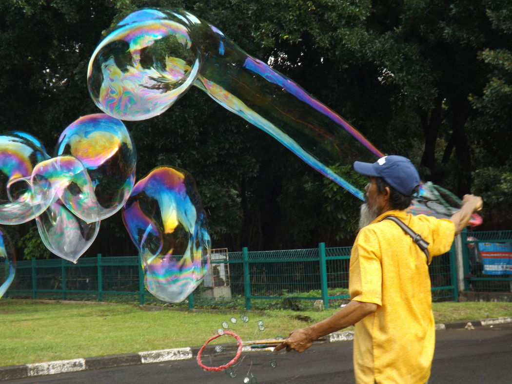 Old man n bubbles..🍎 Outdoors Bubble Wand Bubbles...bubbles...bubbles...bubbles ♡ The EyeEm Photo Bubble Man Bubbles In The Sky Week On Eye Em EyeEm Gallery Multi Colored