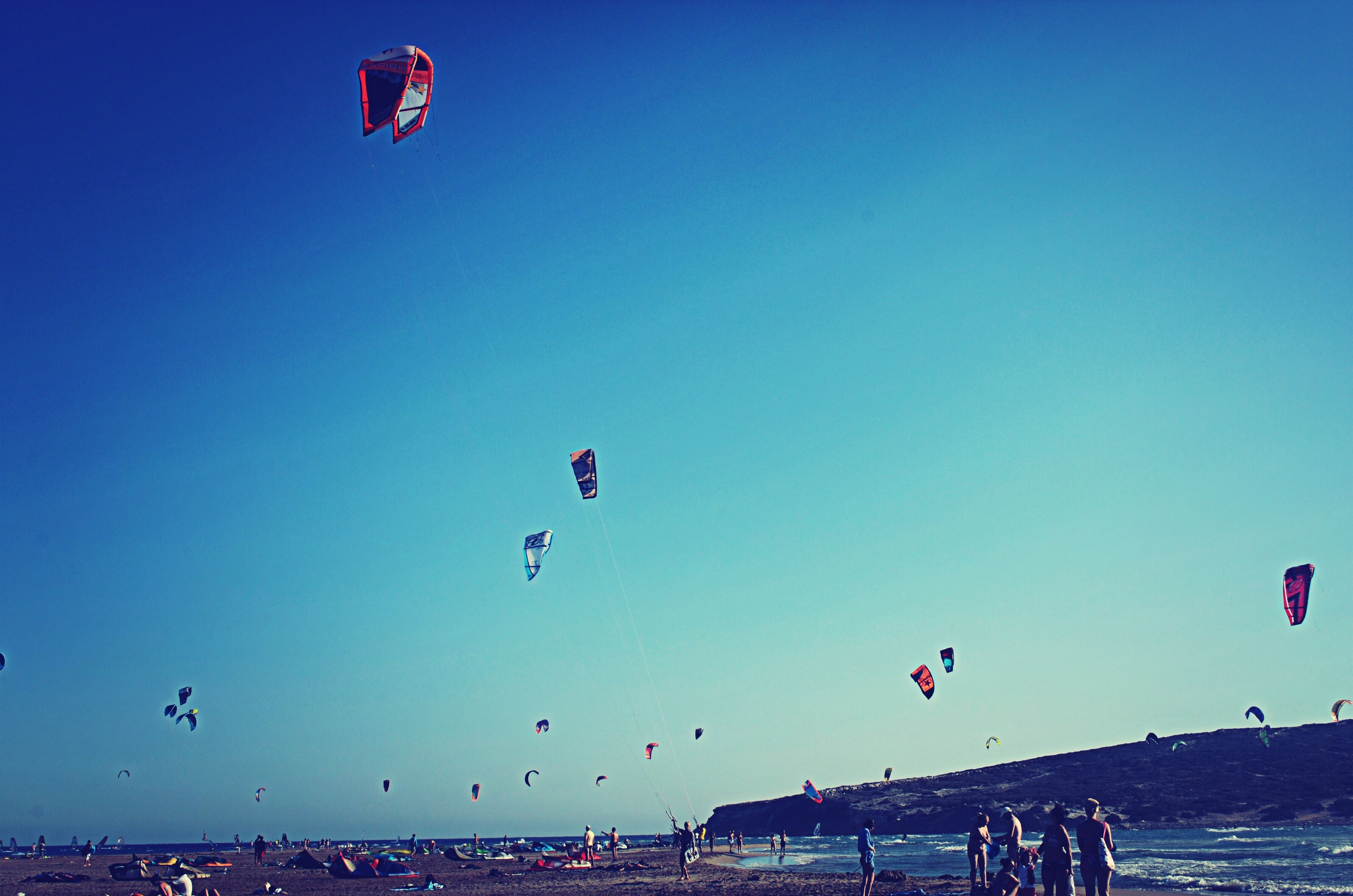 flying, mid-air, leisure activity, parachute, clear sky, extreme sports, lifestyles, paragliding, large group of people, adventure, fun, enjoyment, transportation, vacations, sport, beach, blue, copy space, sea