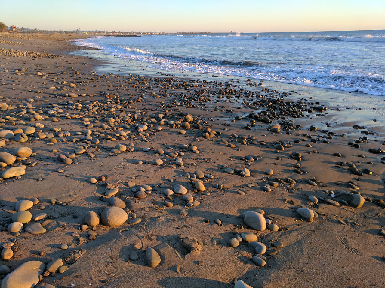 foot prints, rocks and pebbles in sand along ocean side. Beach Coastline Day Footprints Footprints In The Sand Horizon Over Water Nature No People Ocean Oceanscape Outdoors Pebbles And Stones Pebbles On A Beach Rocky Shoreline Sand Sea Sky Water Wave