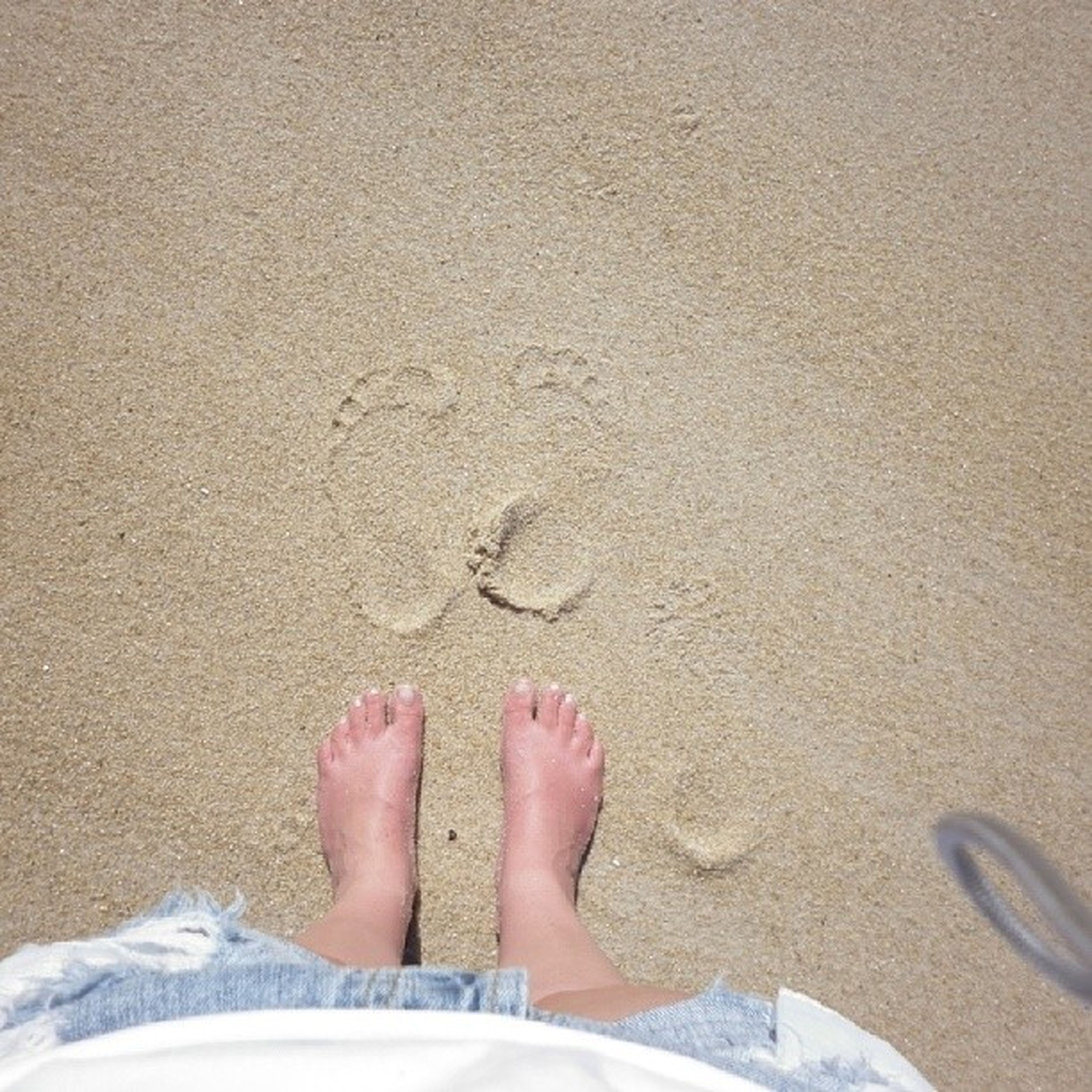 low section, person, personal perspective, sand, beach, human foot, barefoot, shoe, high angle view, lifestyles, shore, leisure activity, part of, standing, outdoors, day, footwear