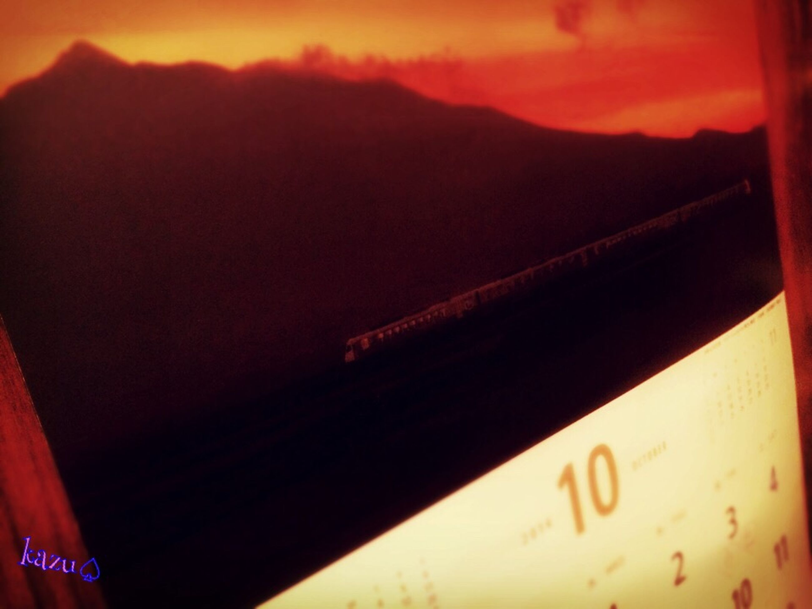 text, communication, western script, sunset, indoors, close-up, orange color, part of, no people, sky, mountain, non-western script, cropped, focus on foreground, illuminated, number, information, low angle view, capital letter, paper