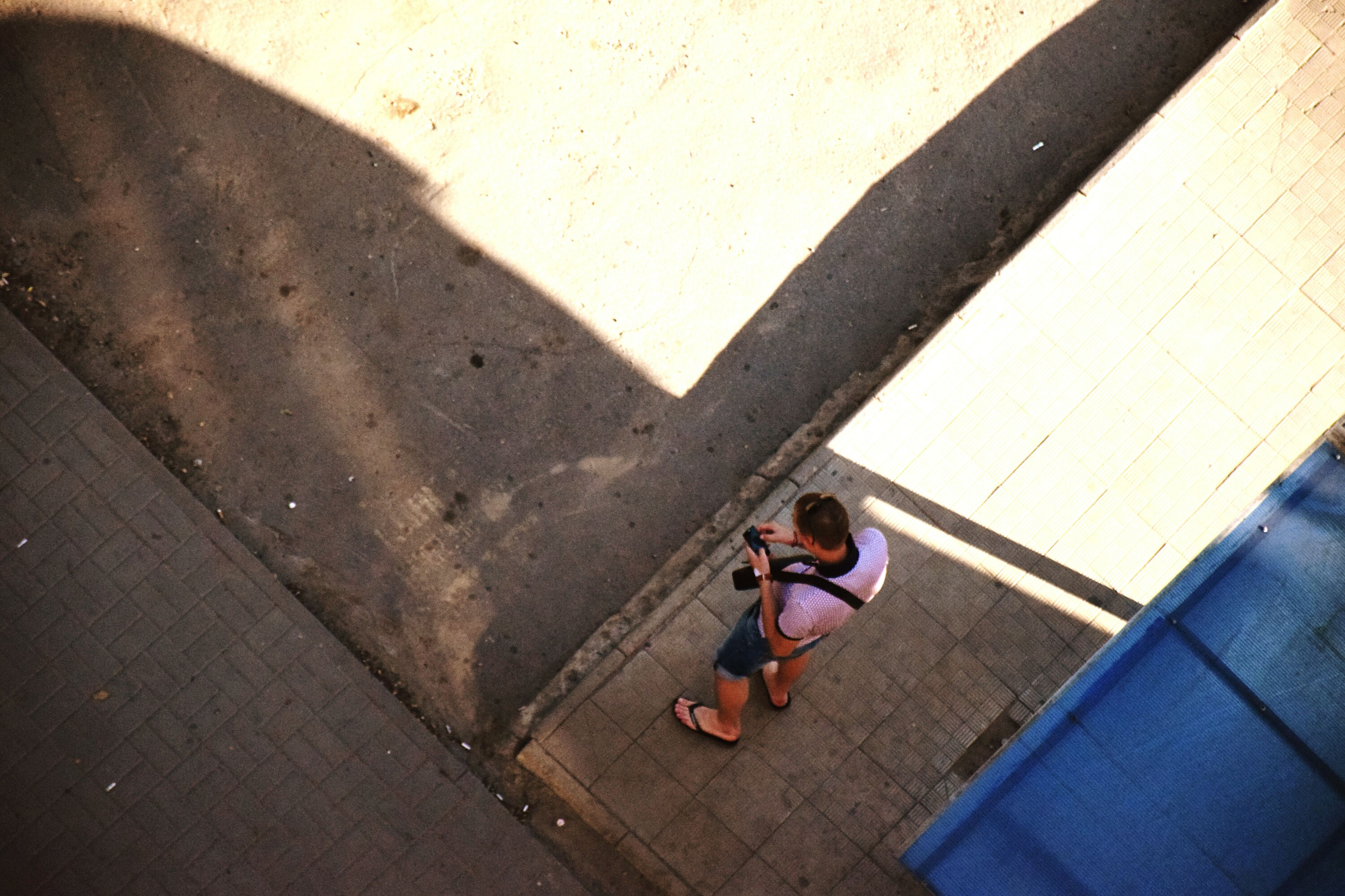 high angle view, sunlight, outdoors, lifestyles, real people, day, childhood, full length, shadow, leisure activity, one person, people, adult