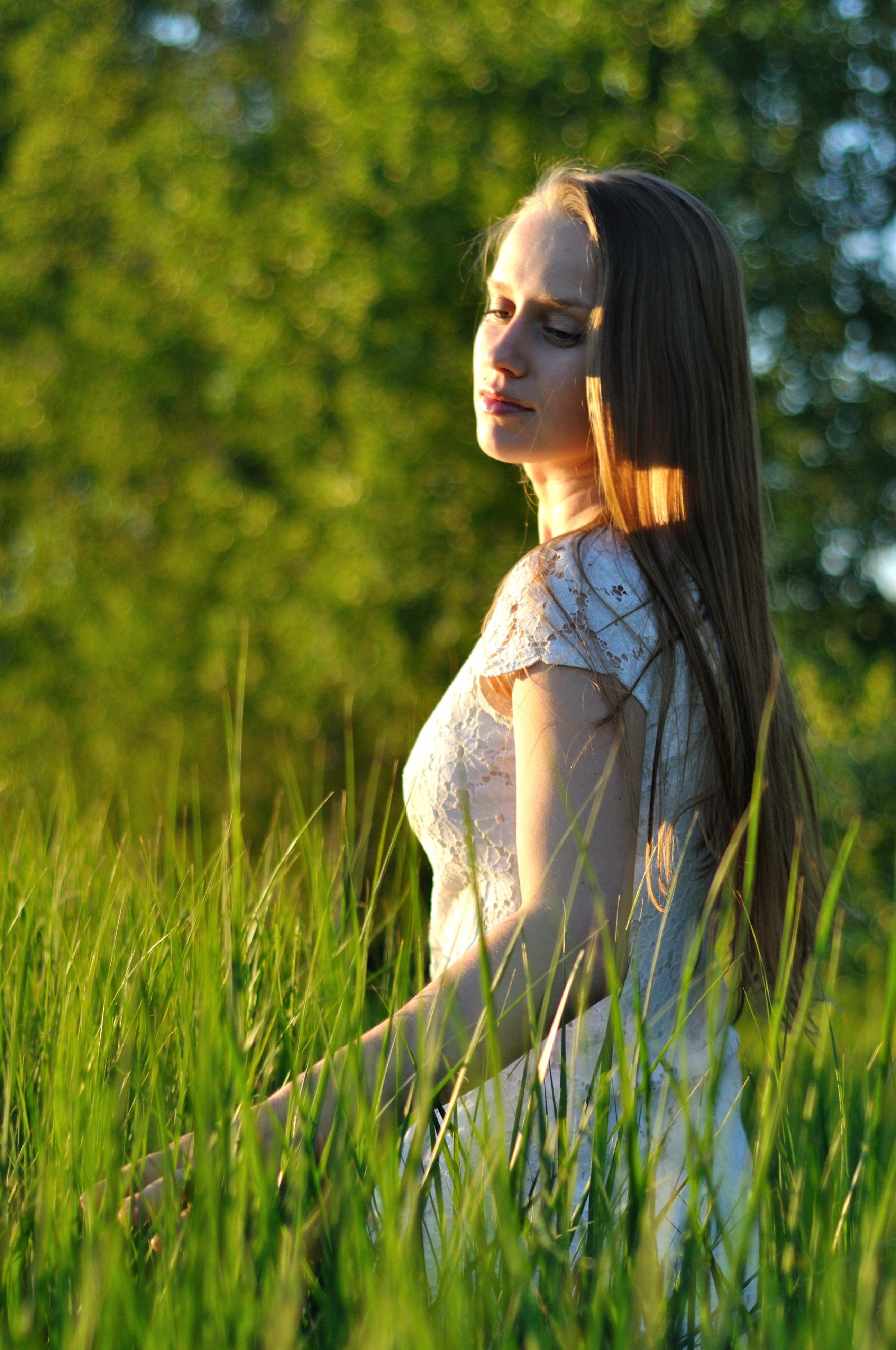 person, young adult, lifestyles, young women, leisure activity, focus on foreground, grass, long hair, casual clothing, three quarter length, side view, field, standing, contemplation, waist up, looking away, nature