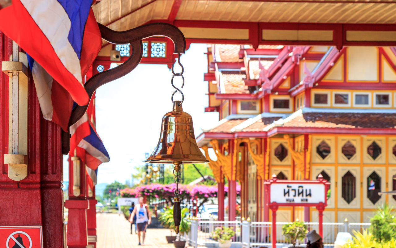 Hua Hin train station's bell and Thai flag Architecture Arrival Bell Building Exterior Built Structure City City Life Commuter Country Countryside Day Hanging Journey Non-western Script Outdoors Railway Station Railway Station Platform Ring Sign Station Thai Culture Thai Flag Thailand Train Station Travel