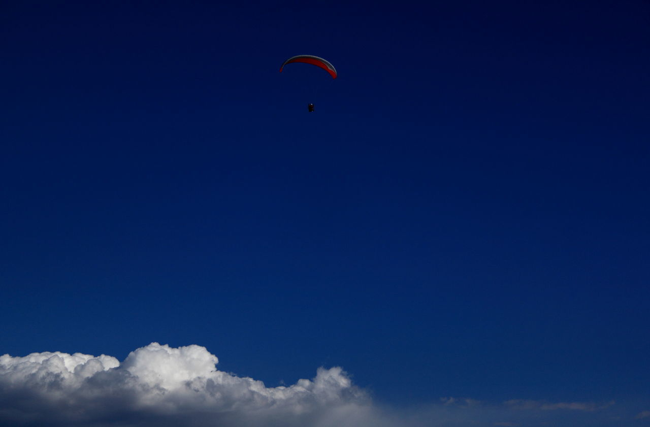 blue, parachute, outdoors, real people, adventure, low angle view, extreme sports, mid-air, leisure activity, sky, day, one person, paragliding, nature, sport, beauty in nature, people