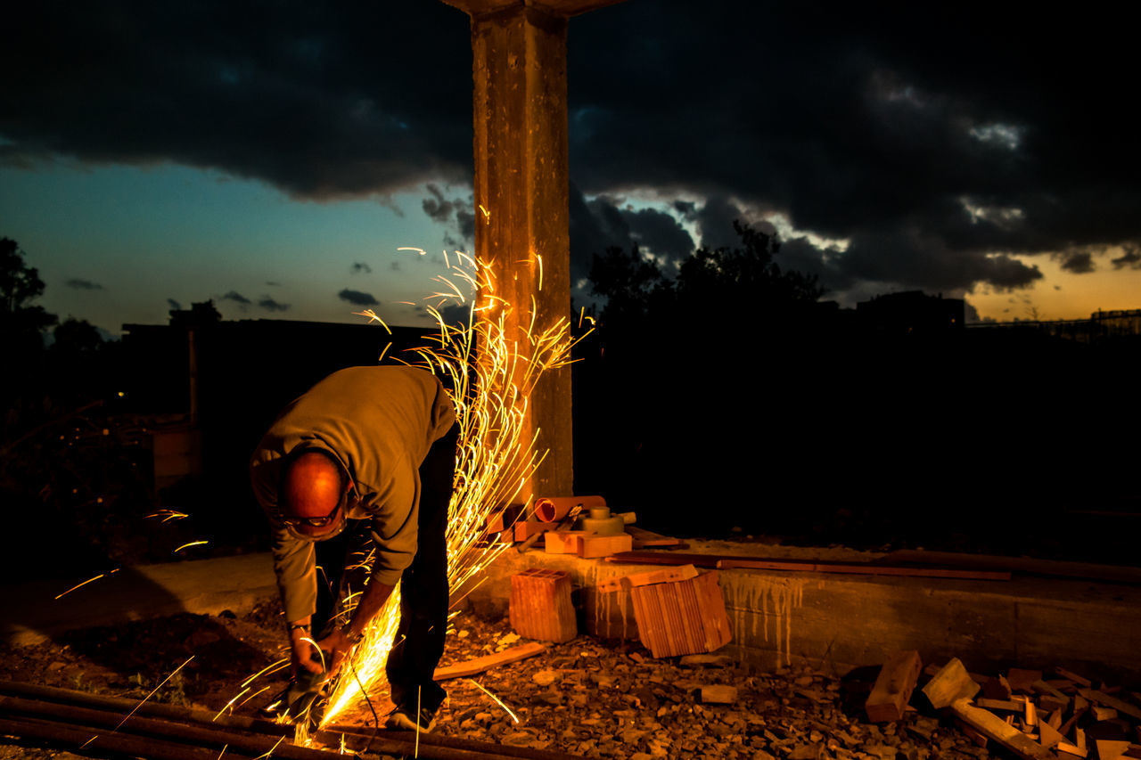 Worker Cutting Metal Against Cloudy Sky At Dusk