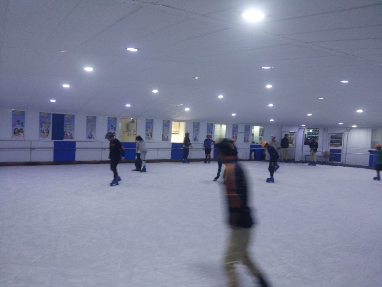 illuminated, leisure activity, lighting equipment, indoors, built structure, real people, walking, ice-skating, winter sport, men, ice rink, sport, lifestyles, women, architecture, ice skate, competition, day, people