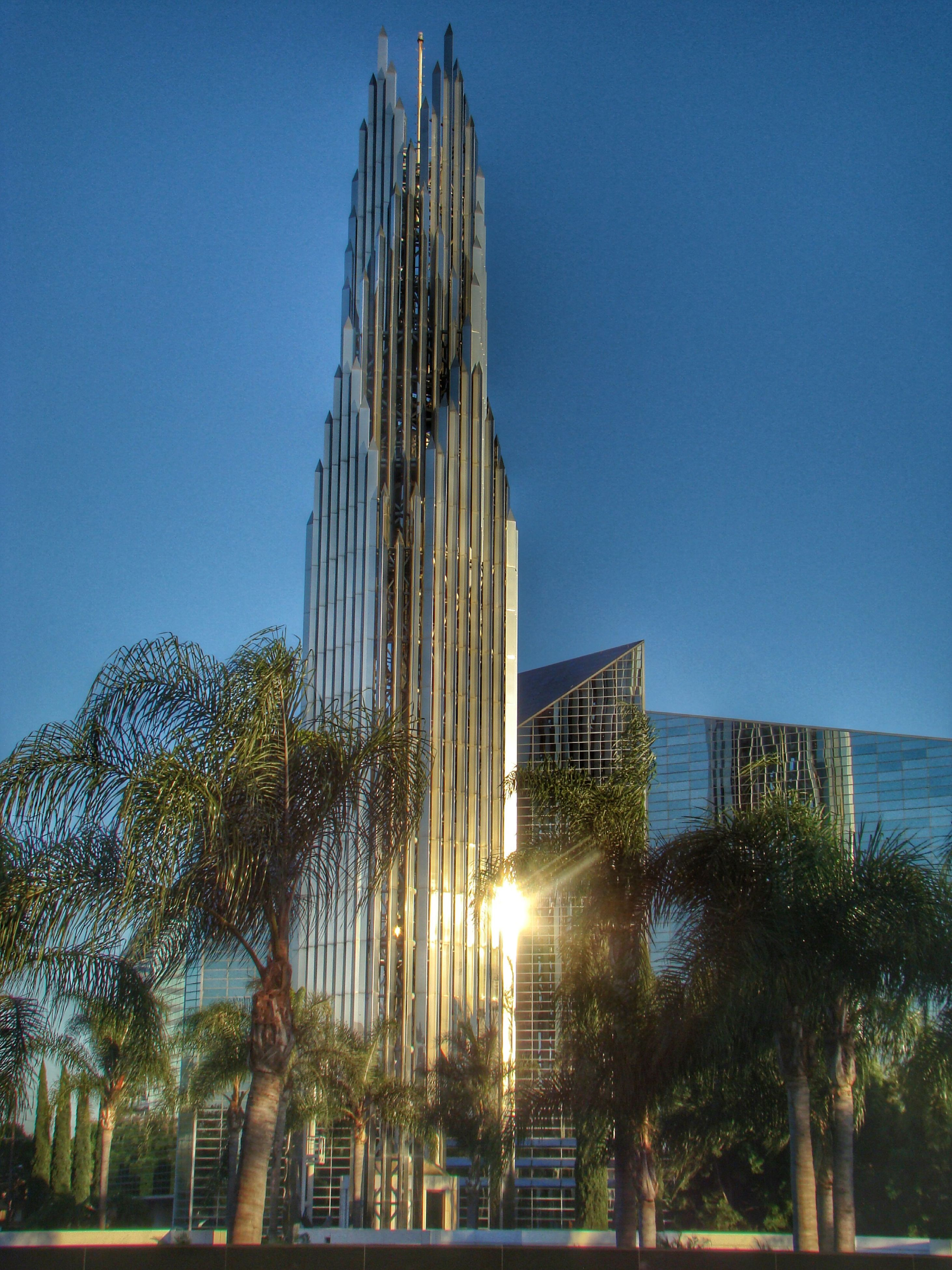clear sky, built structure, architecture, blue, sunlight, building exterior, water, sun, tree, low angle view, palm tree, tall - high, sea, city, sunbeam, copy space, modern, lens flare, tower, reflection