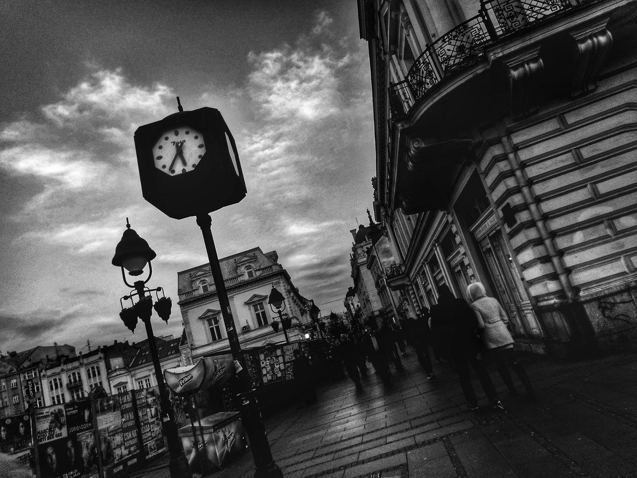 Tilt Image Of Clock On Sidewalk By Building Against Sky