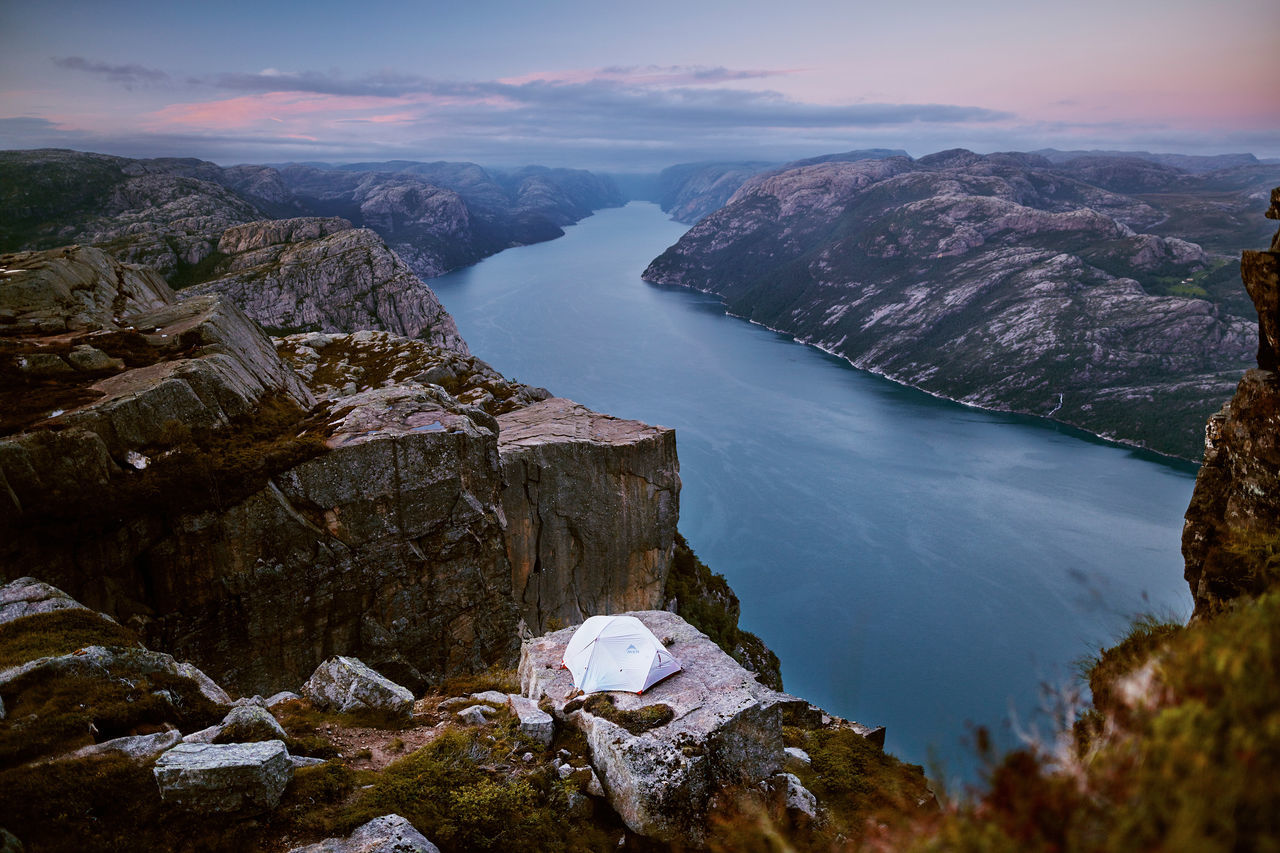 A tent with people sleeping inside, while the sun is slowly going down. Adventure Beauty In Nature Cliff Fjord High Landscape Lysefjorden Mountain Nature Norge Norgeibilder Norway Norway🇳🇴 Outdoorlife Outdoors Pink Preikestolen Pulpitrock Purple Summit Sundown Sunset Tent Travel Visitnorway