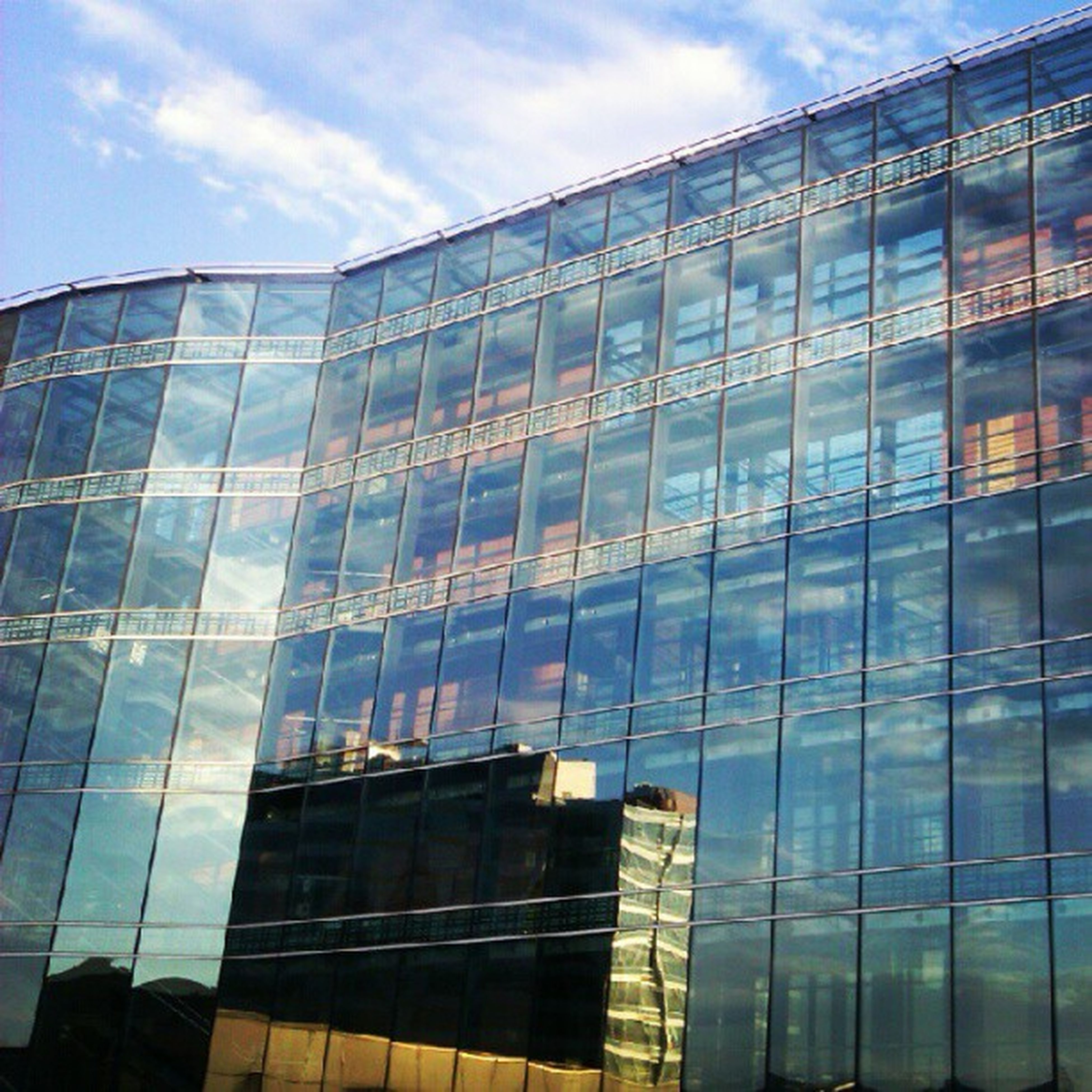 architecture, built structure, building exterior, low angle view, modern, glass - material, reflection, office building, sky, city, building, skyscraper, cloud - sky, window, tall - high, glass, tower, cloud, day, no people