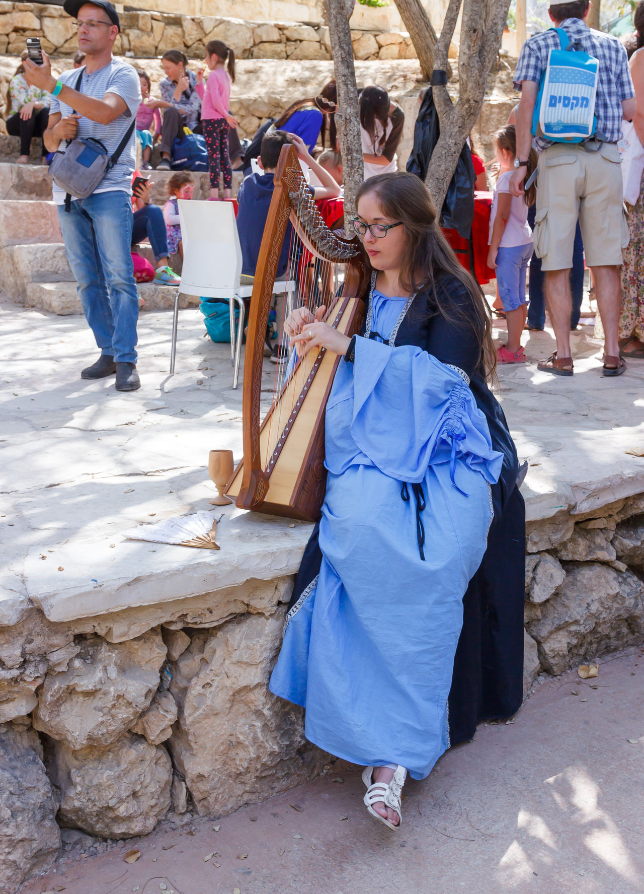 "Jerusalem, Israel, October 03, 2016: Member of the annual festival of ""Knights of Jerusalem"" dressed as a citizen playing the harp in Jerusalem, Israel Ancient Annual Attraction Christian Citizen Decorations Dressed Event Famous Festival History Holy Israel Jerusalem Knight  Land Medieval Member Old Performance Performs Photographer Pose Sword Tradition"
