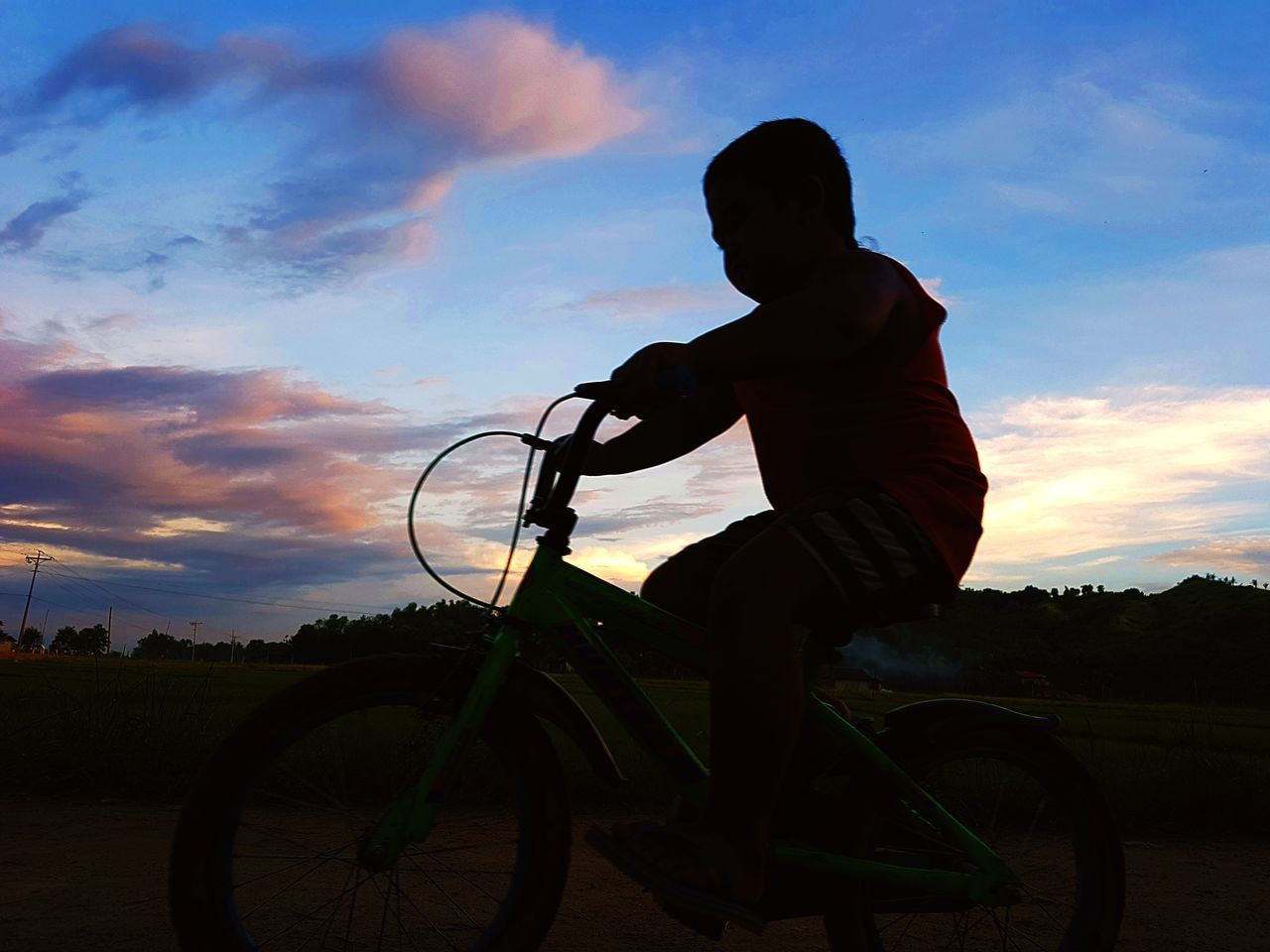 bicycle, real people, transportation, sky, one person, sunset, cycling, mode of transport, land vehicle, silhouette, cloud - sky, men, lifestyles, riding, outdoors, leisure activity, bmx cycling, nature, mountain bike, full length, day, cycling helmet, people