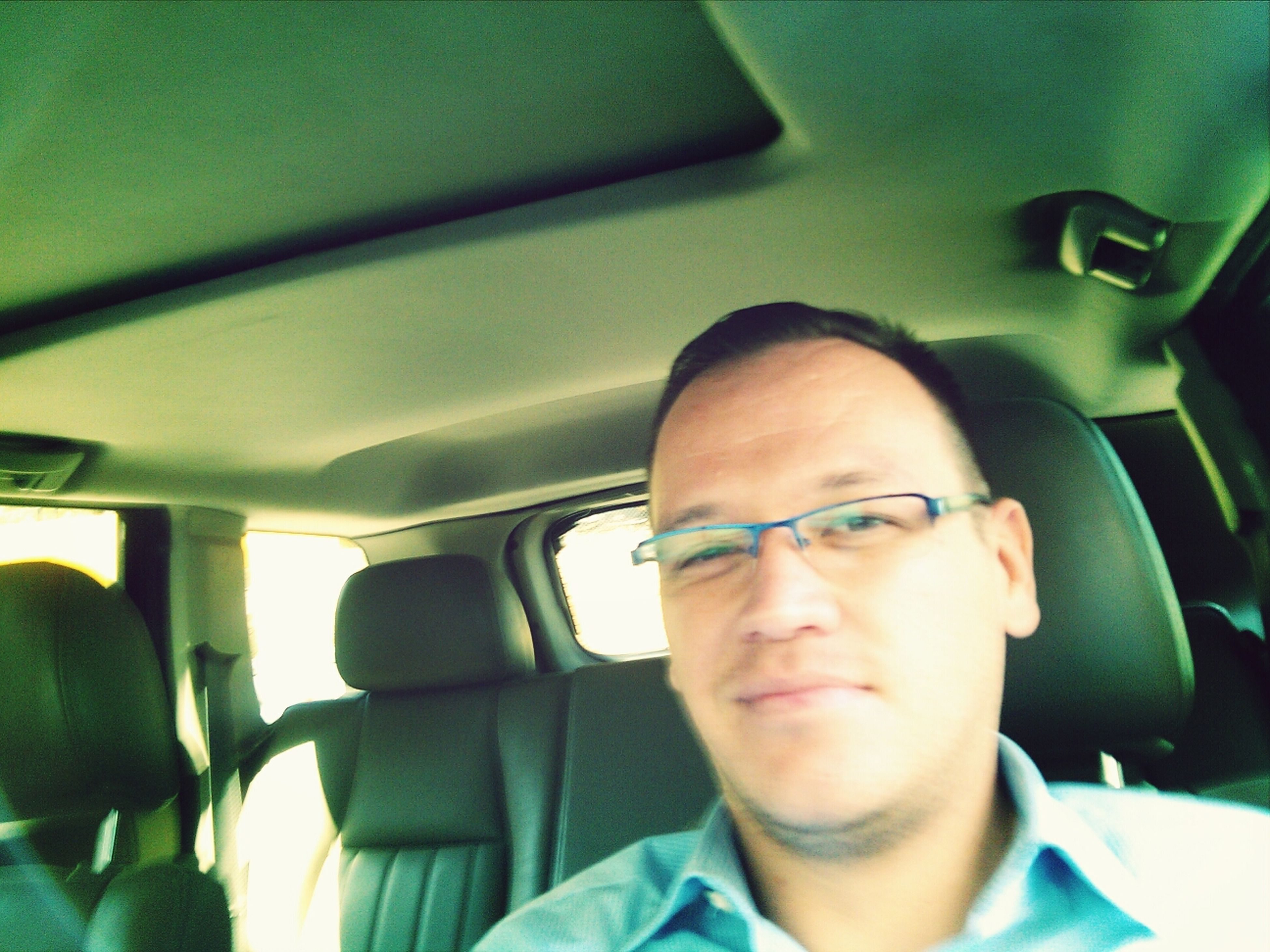 vehicle interior, indoors, transportation, mode of transport, lifestyles, vehicle seat, car interior, car, sitting, land vehicle, travel, headshot, window, leisure activity, young adult, portrait, relaxation, looking at camera