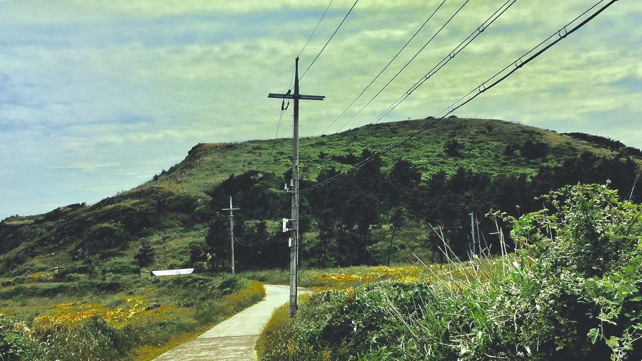 cable, connection, power line, sky, electricity, day, electricity pylon, no people, outdoors, cloud - sky, mountain, low angle view, nature, tranquility, landscape, tree, technology, telephone line, beauty in nature, grass