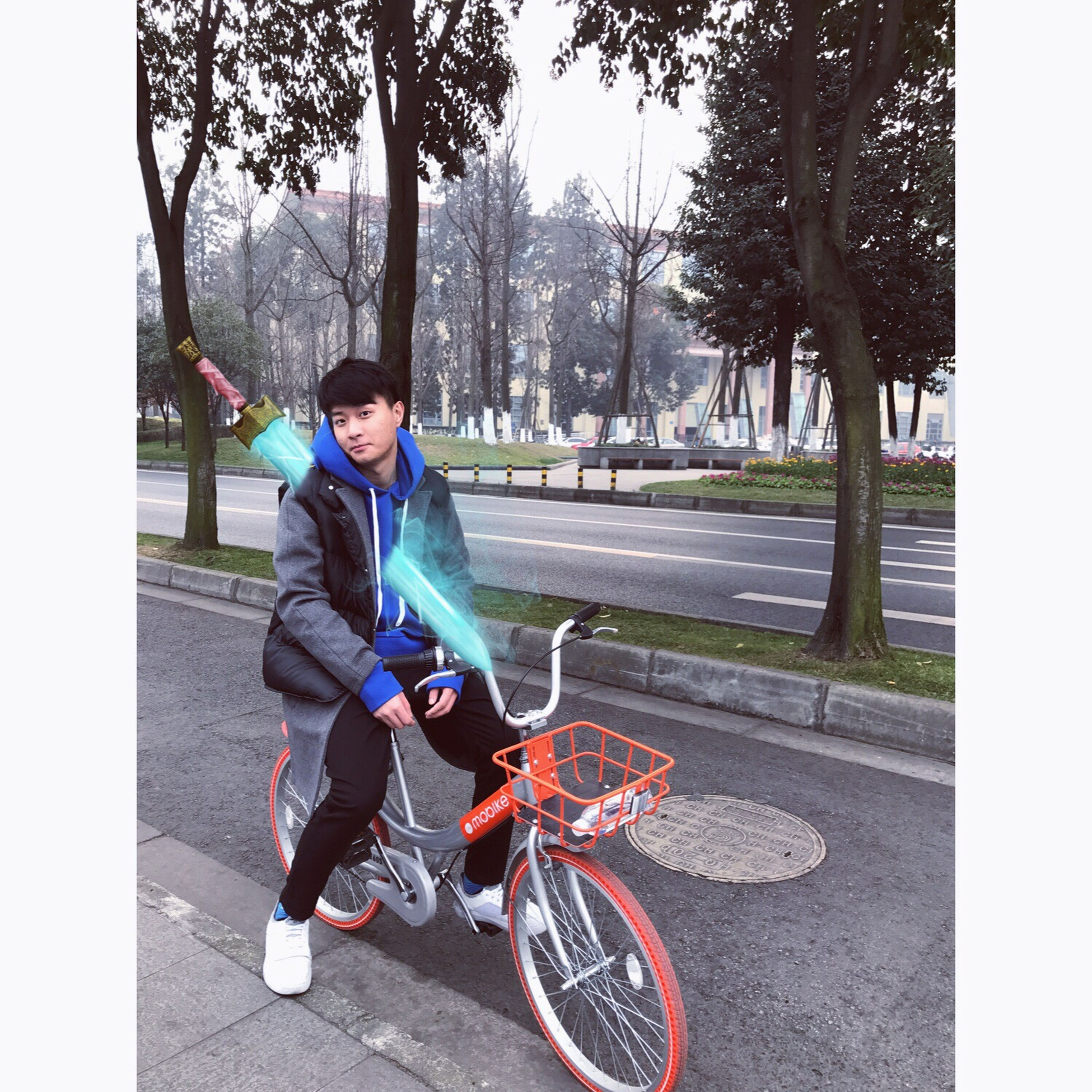 full length, tree, leisure activity, sitting, riding, one person, lifestyles, only men, outdoors, one man only, cycling, day, sports clothing, headwear, people, adults only, young adult, adult