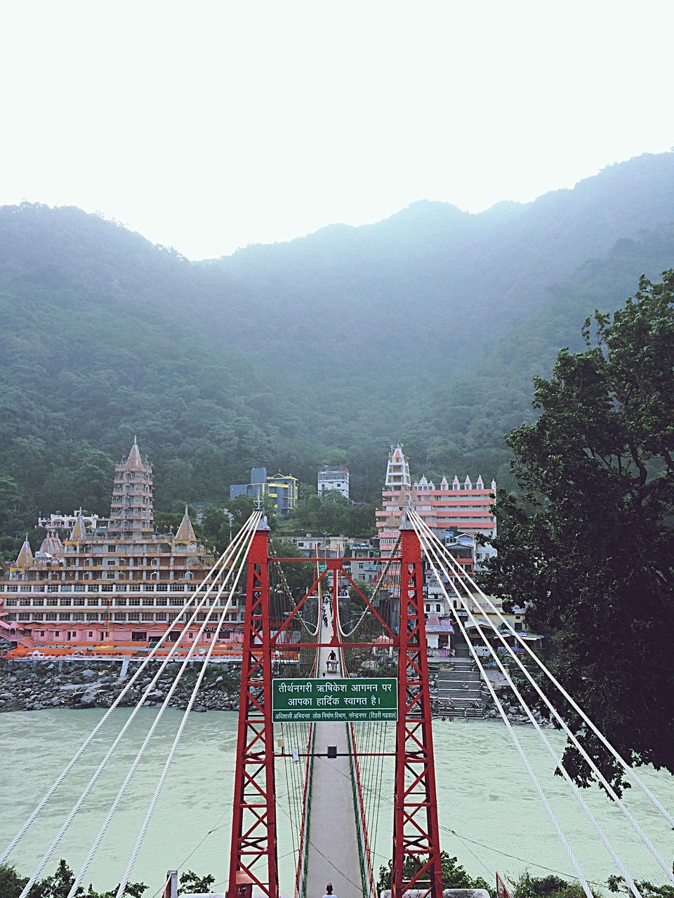 mountain, architecture, built structure, connection, day, bridge - man made structure, transportation, outdoors, tree, high angle view, clear sky, nature, mountain range, suspension bridge, building exterior, river, no people, sky, travel destinations, beauty in nature, water