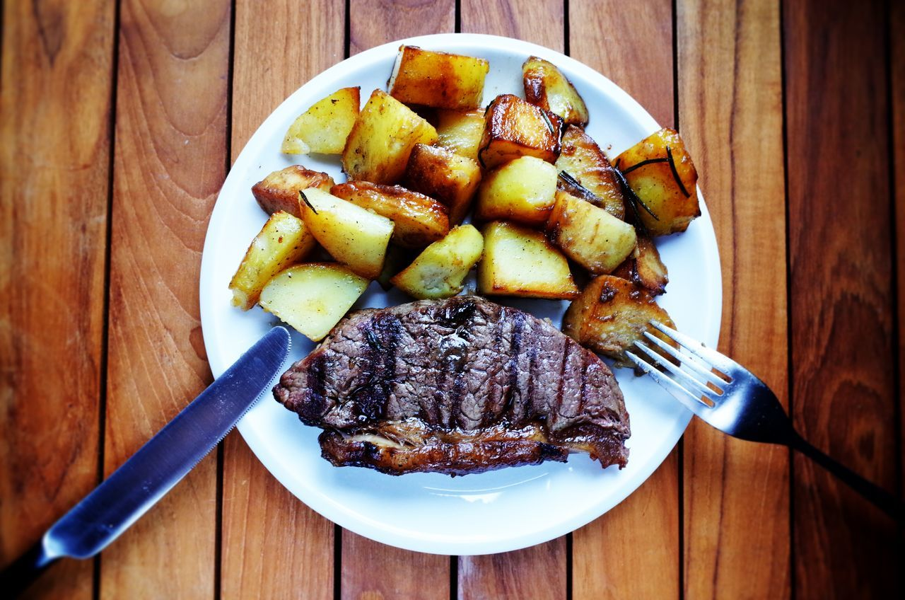 Close-Up Of Steak With Potatoes Served In Plate On Table
