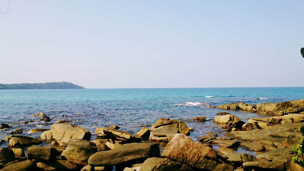 sea, water, clear sky, horizon over water, copy space, tranquil scene, scenics, rock - object, tranquility, beauty in nature, nature, stone - object, beach, shore, idyllic, rock, pebble, sky, outdoors, day