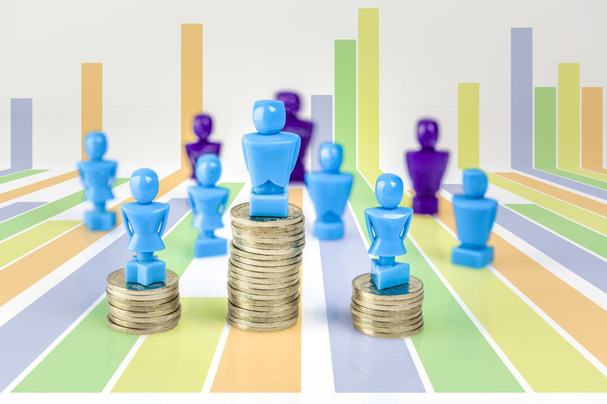 Male and female figurines standing on top of coin piles with other figurines in the background and bar graph. Wage gap and corporate structure concept. Bar Graph Blue Business Business Finance And Industry Chess Chess Piece Close-up Coins Day Female Figurines  Gender Equality Indoors  Leisure Games Male No People Pile Of Coins Strategy Studio Shot Wage Gap White Background