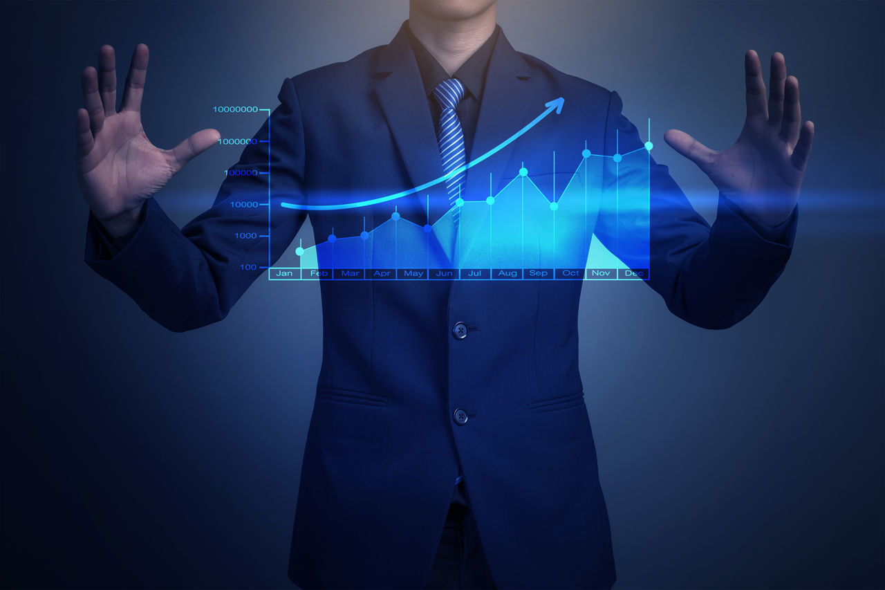 Digitally Generated Image Of Businessman Showing Graph Representing Growth Against Colored Background