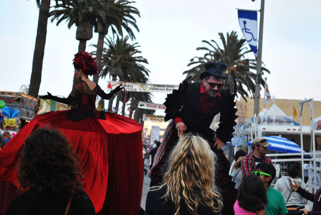 At The Fair Black Suit California Palms Costumes Entertaining In Costume In The Crowd On Stilts On The Street Outdoors Red Dress Red Feathers Red Shirt Top Hat