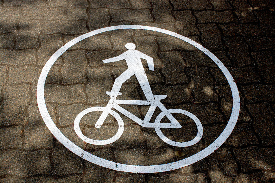 "a traffic sign showin a man ""standing"" on a bike Acrobat Bike Fahrrad Footpath Fußgänger Information Pattern Pflaster Shadow Sign Straße Street Symbol Traffic Traffic Sign Verkehrszeichen Weiss"