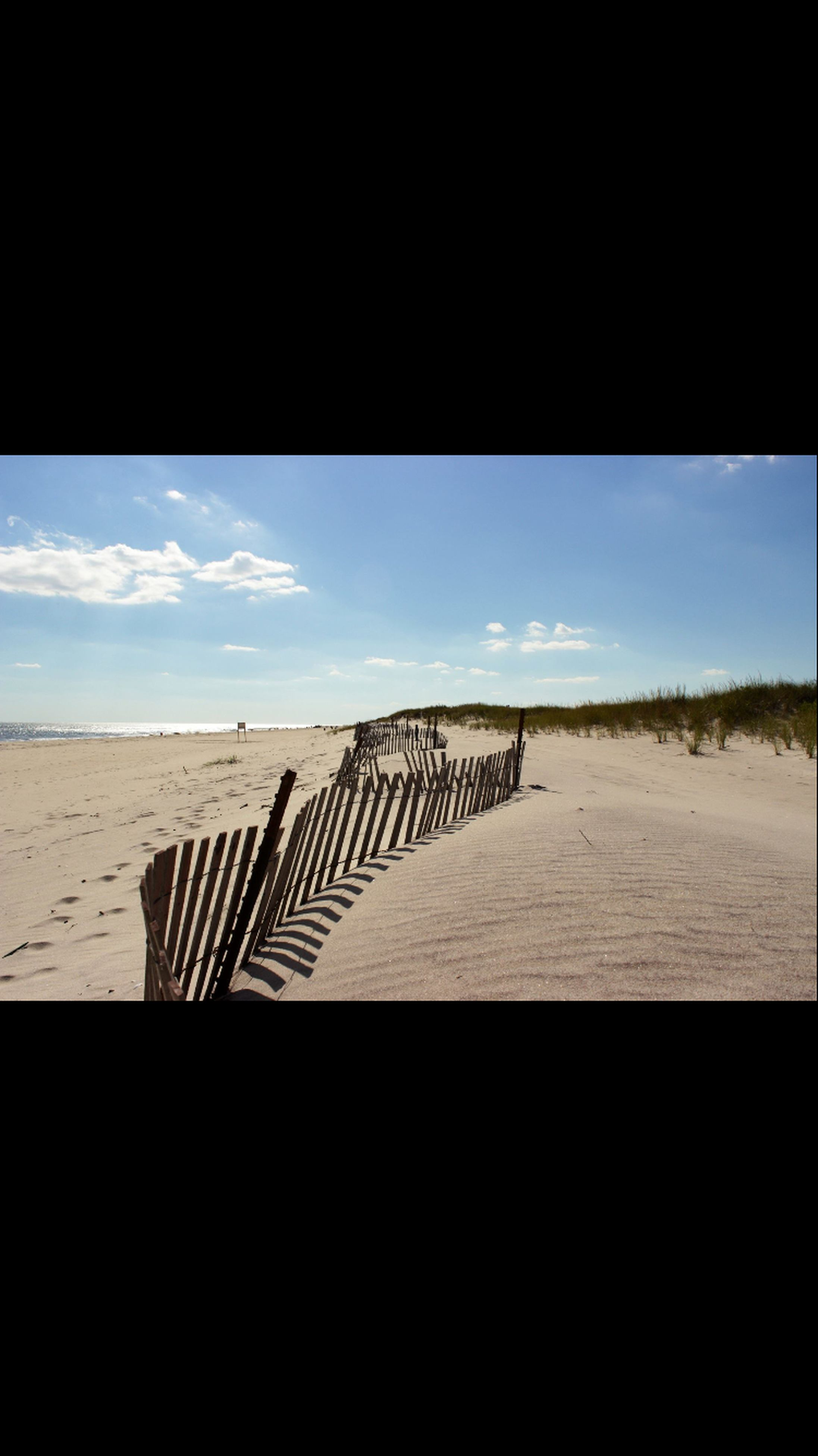 sky, sand, shadow, sunlight, beach, wood - material, day, tranquility, no people, nature, outdoors, absence, tranquil scene, cloud, pattern, cloud - sky, wood, wooden, copy space, low angle view